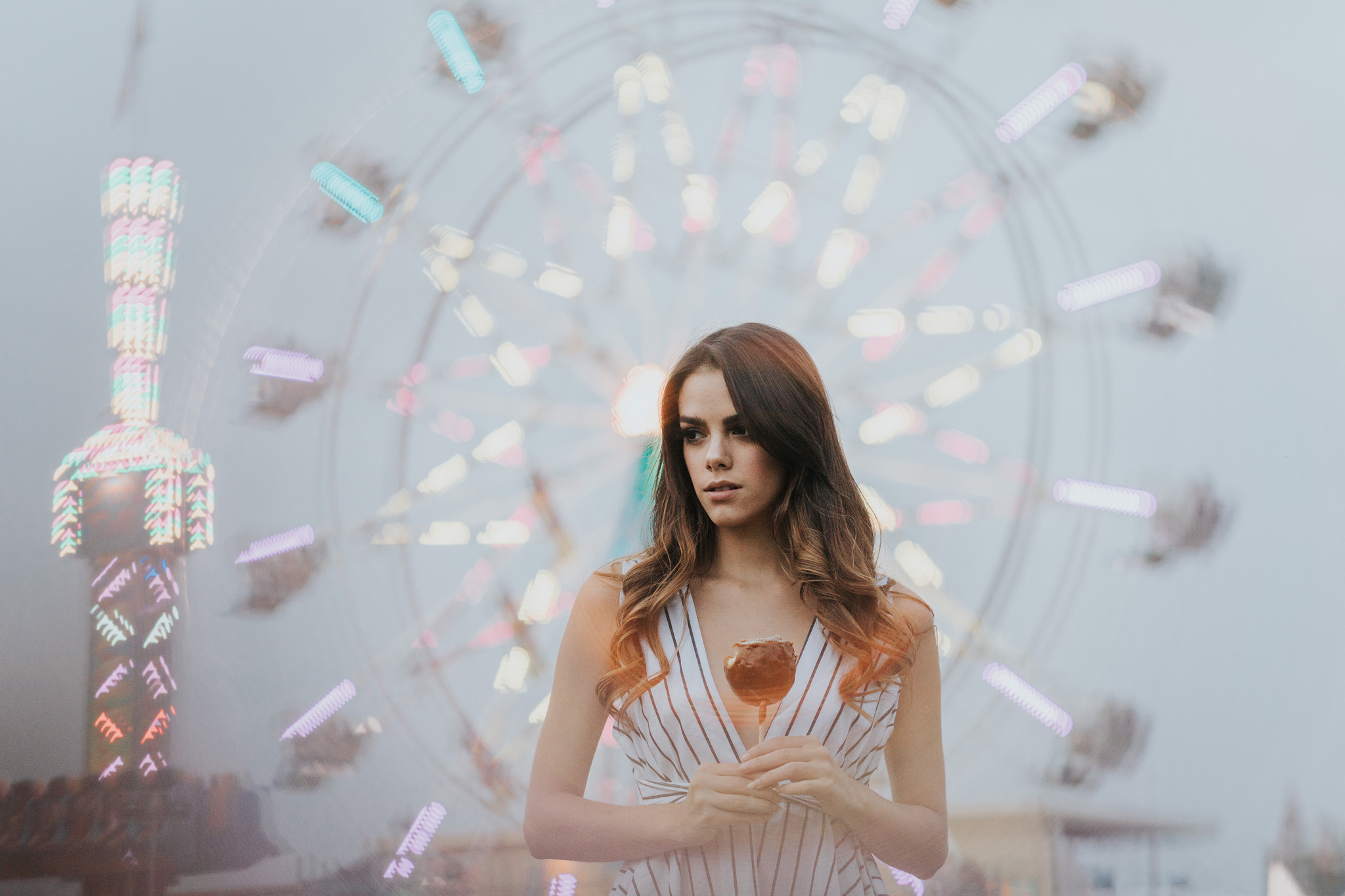 model holding candy apple in front of ferris wheel at the fair
