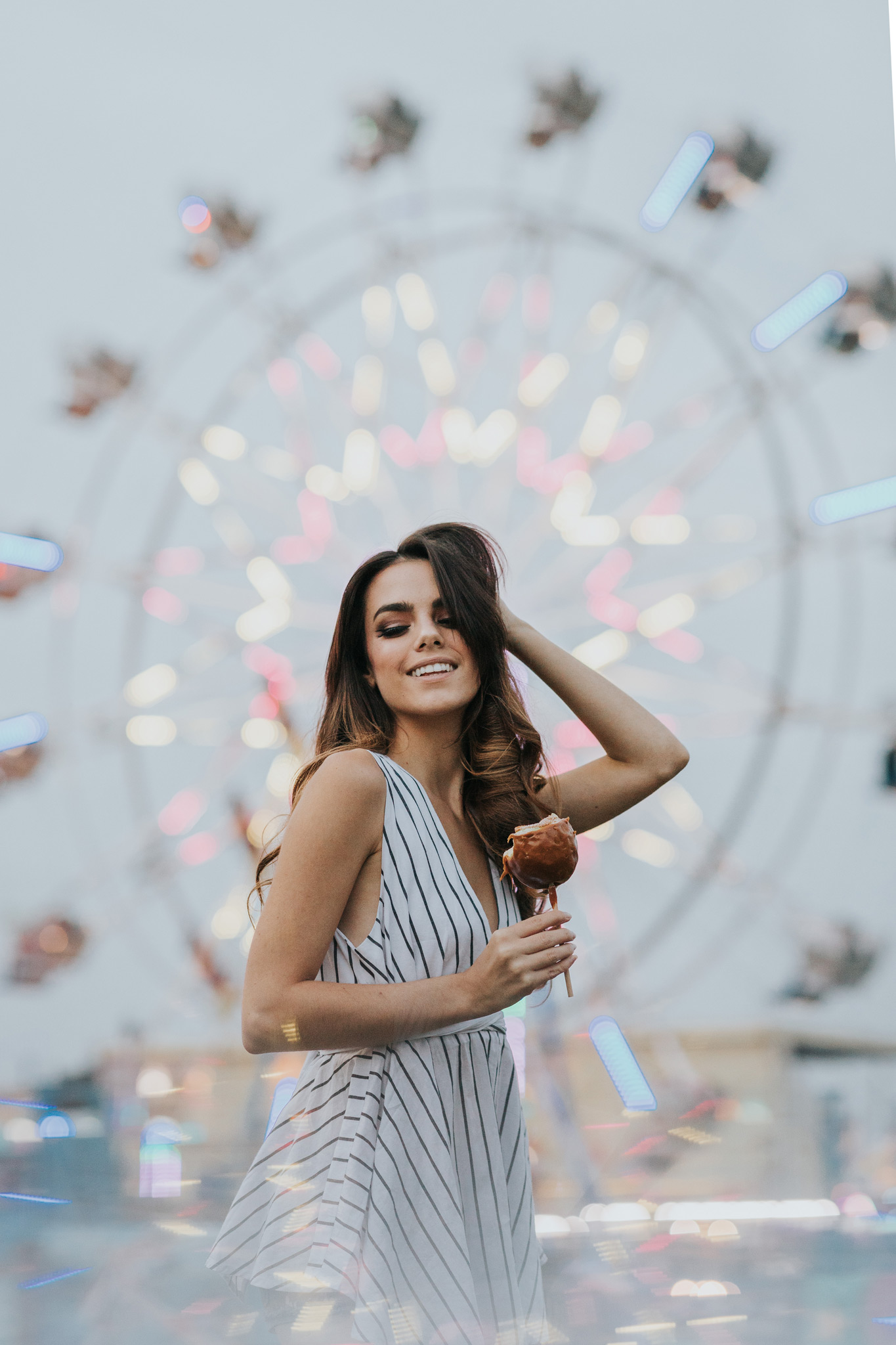 model smiling holding candy apple at stampede ferris wheel