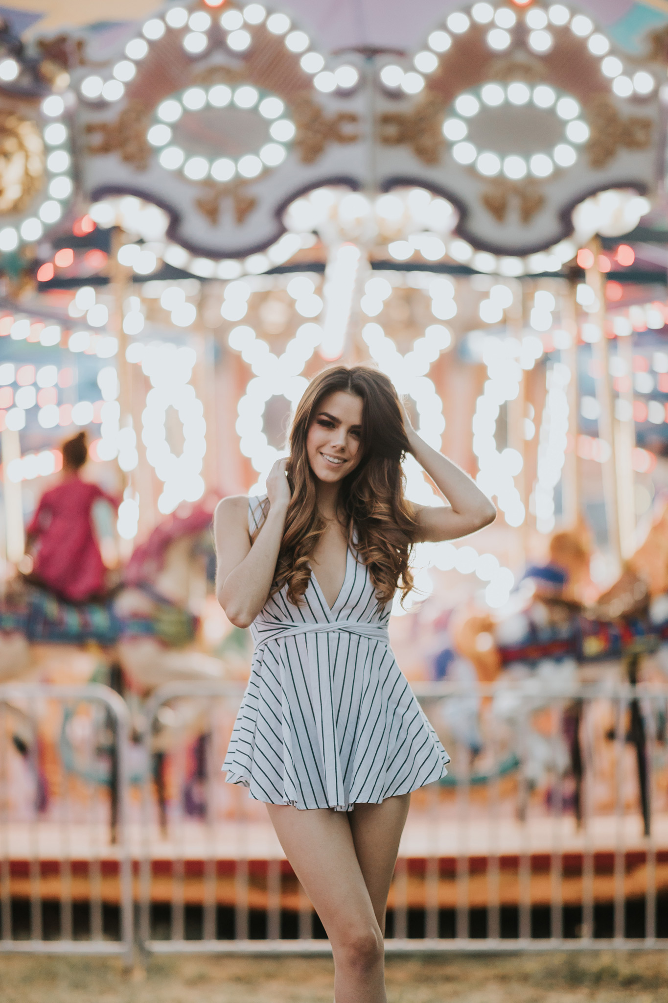 model posing in front of merry-go-round smiling