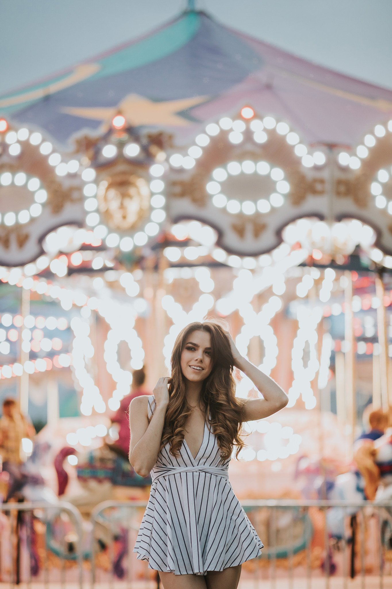 model posing in front of carousel lights at night medicine hat stampede