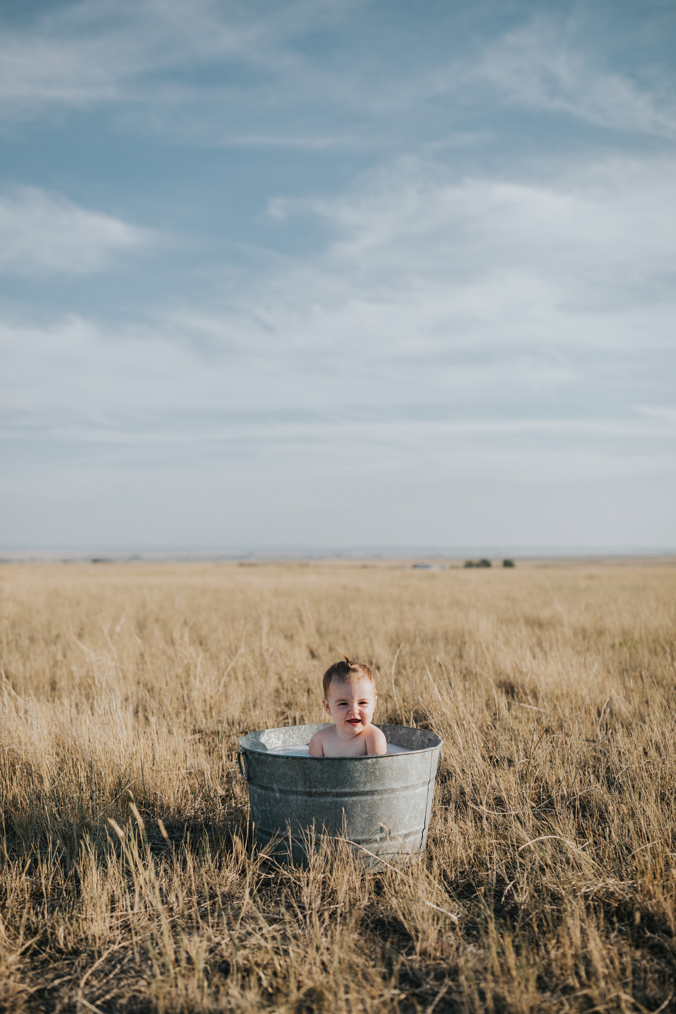 baby sitting in round metal tub milk bath smiling alberta farm