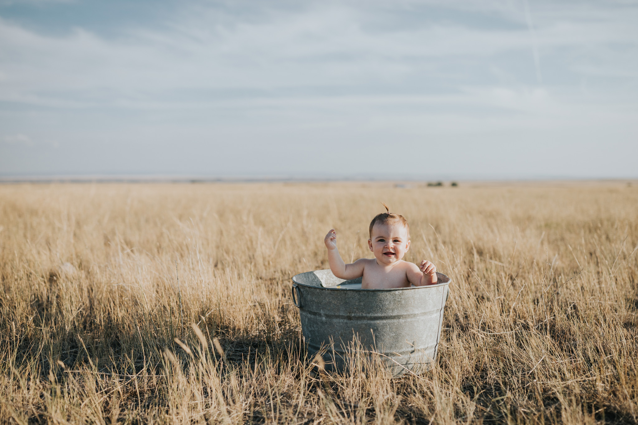 baby sitting in round metal tub milk bath smiling irvine alberta farm