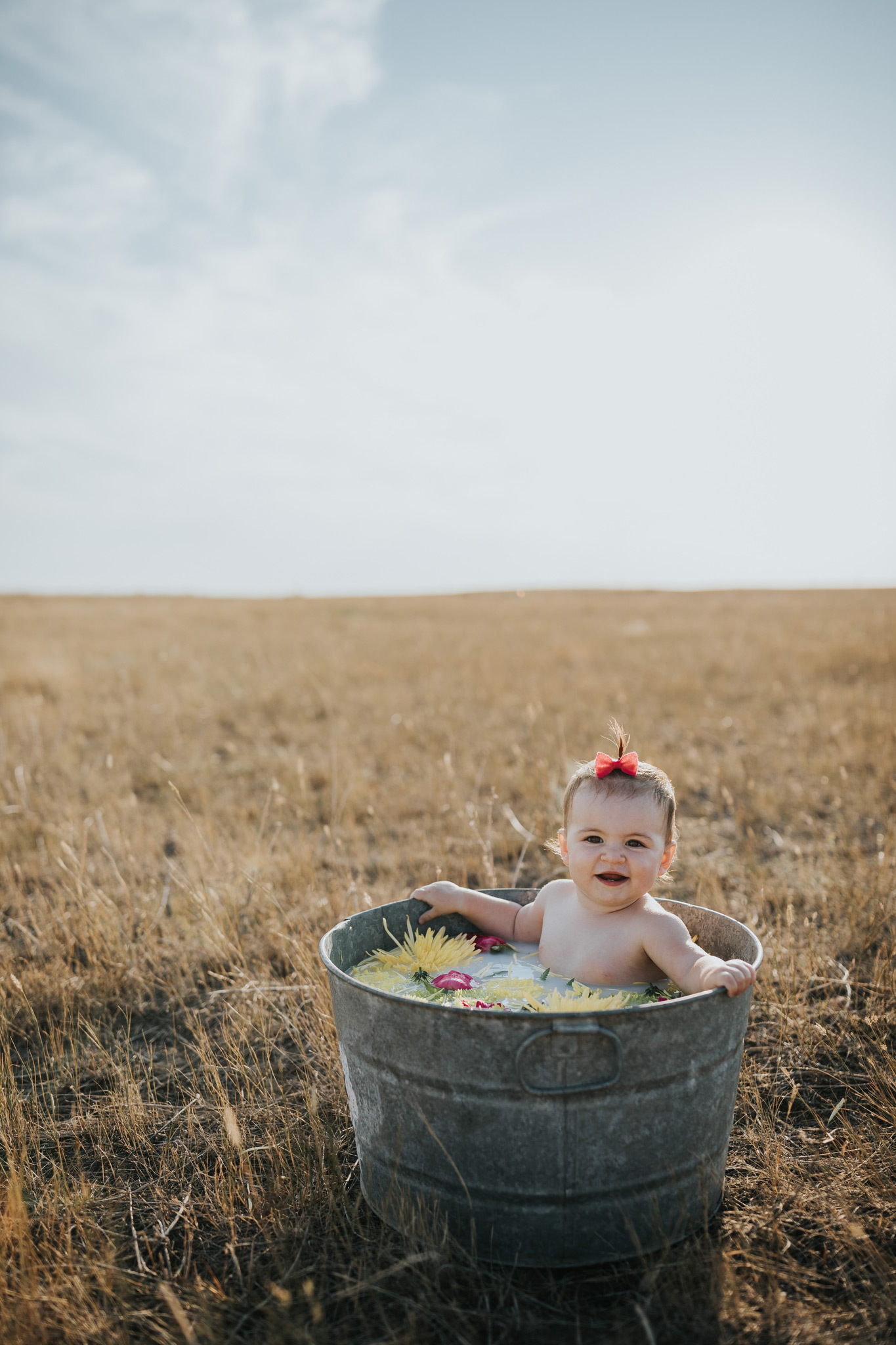 baby relaxing in round metal tub milk bath with flowers