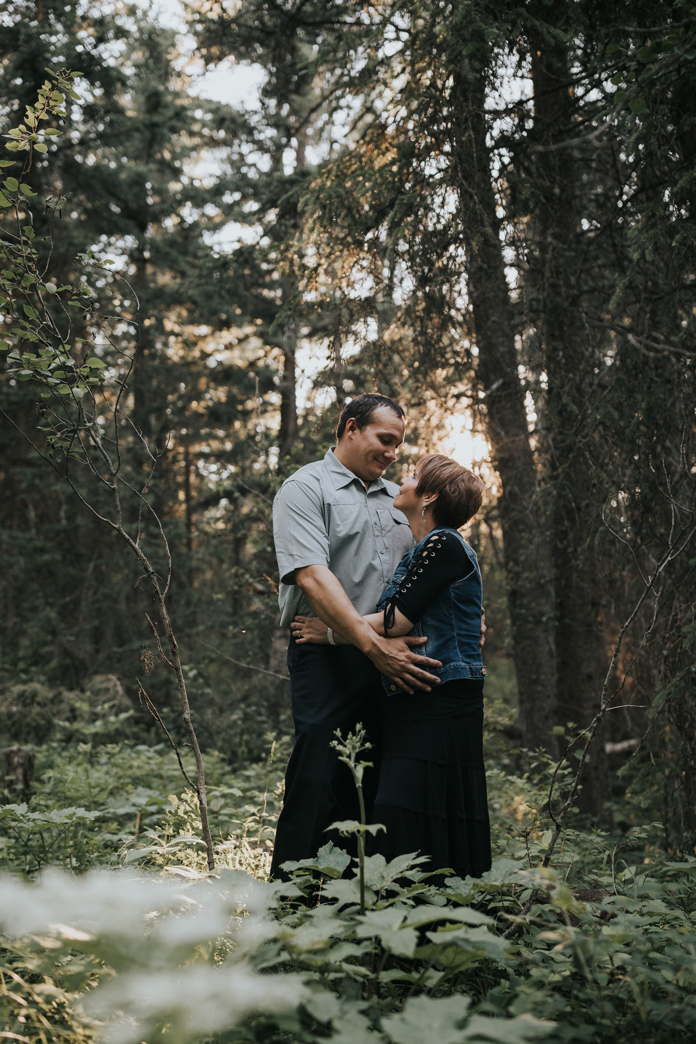 engaged couple standing together in forest spruce coulee campground