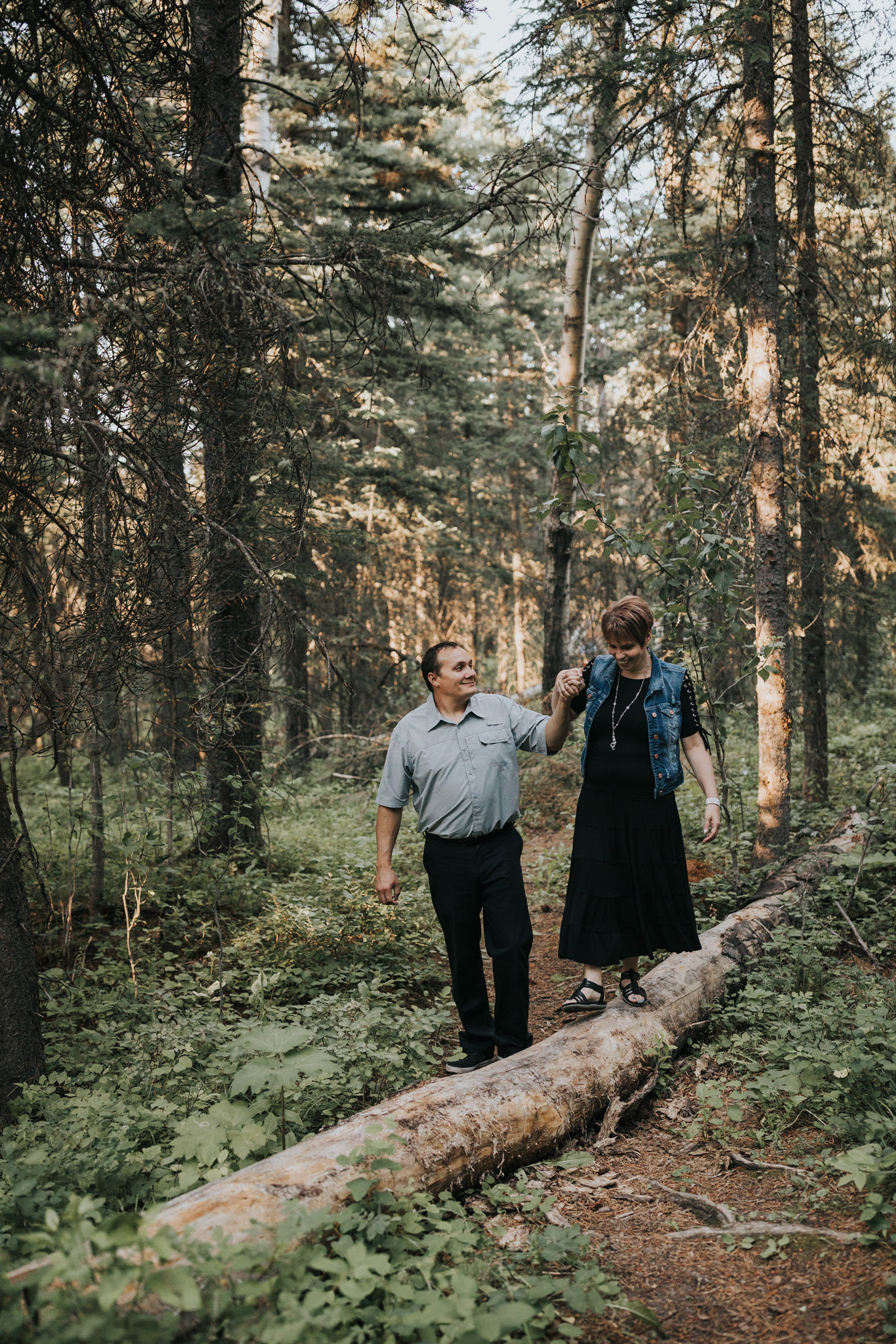 man holding fiancé's hand as she walks across fallen tree log engagement photo