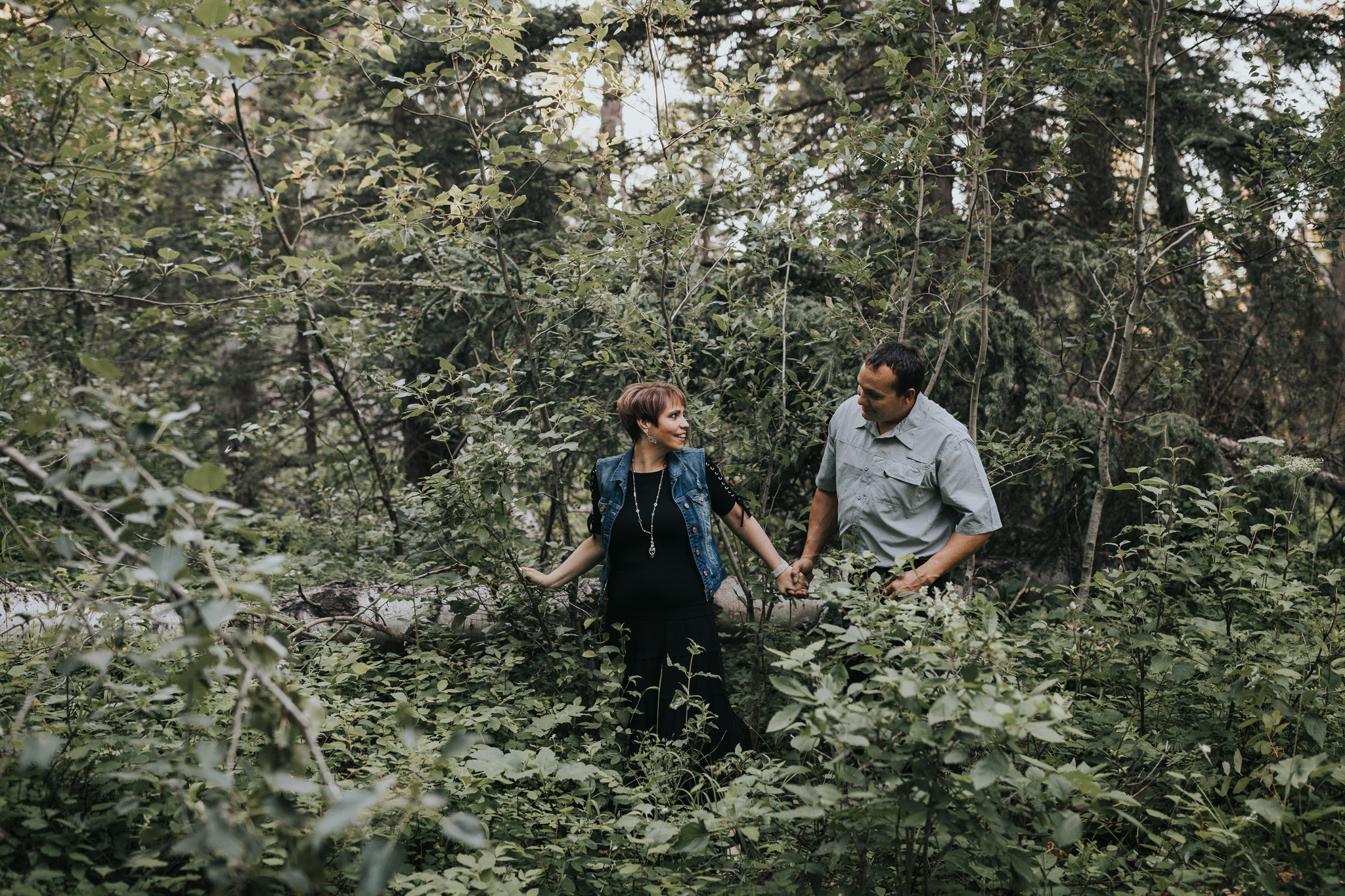 couple walking through forest brush smiling engagement photo