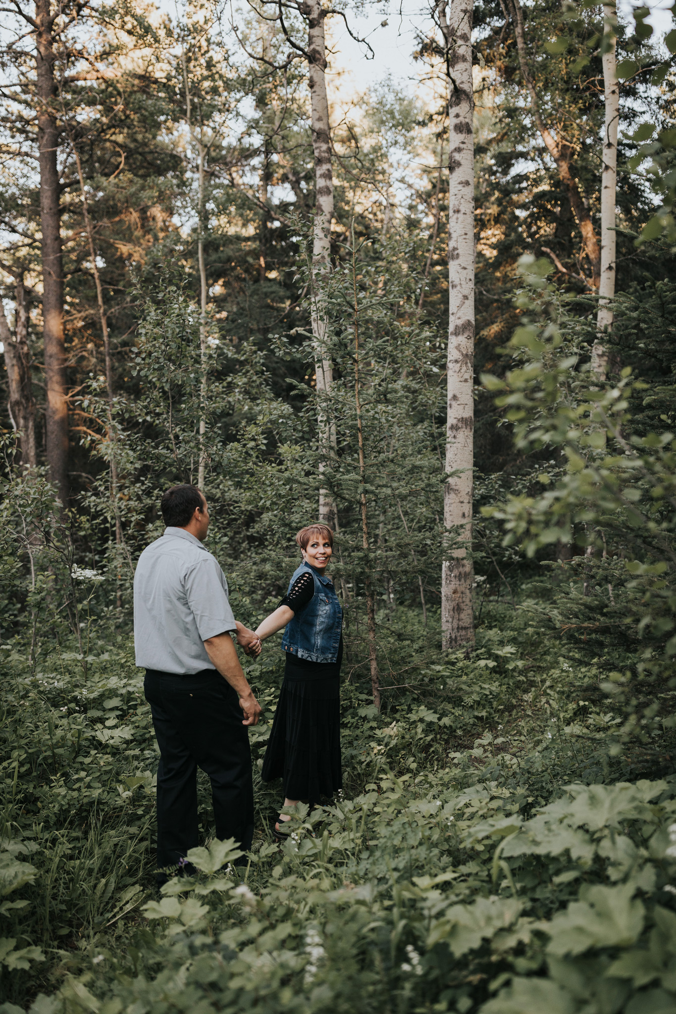 engaged couple wandering through forest greenery spruce coulee