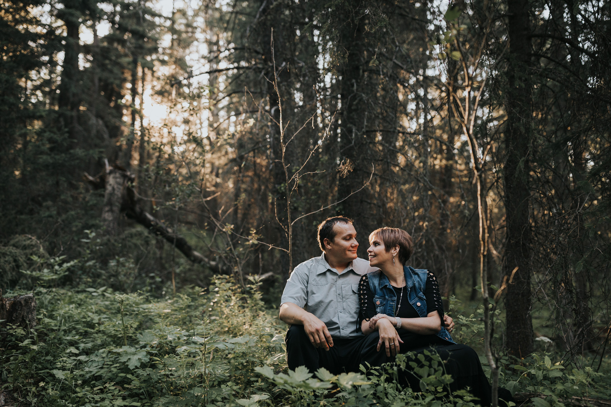 couple sitting on tree log in forest cypress hills engagement