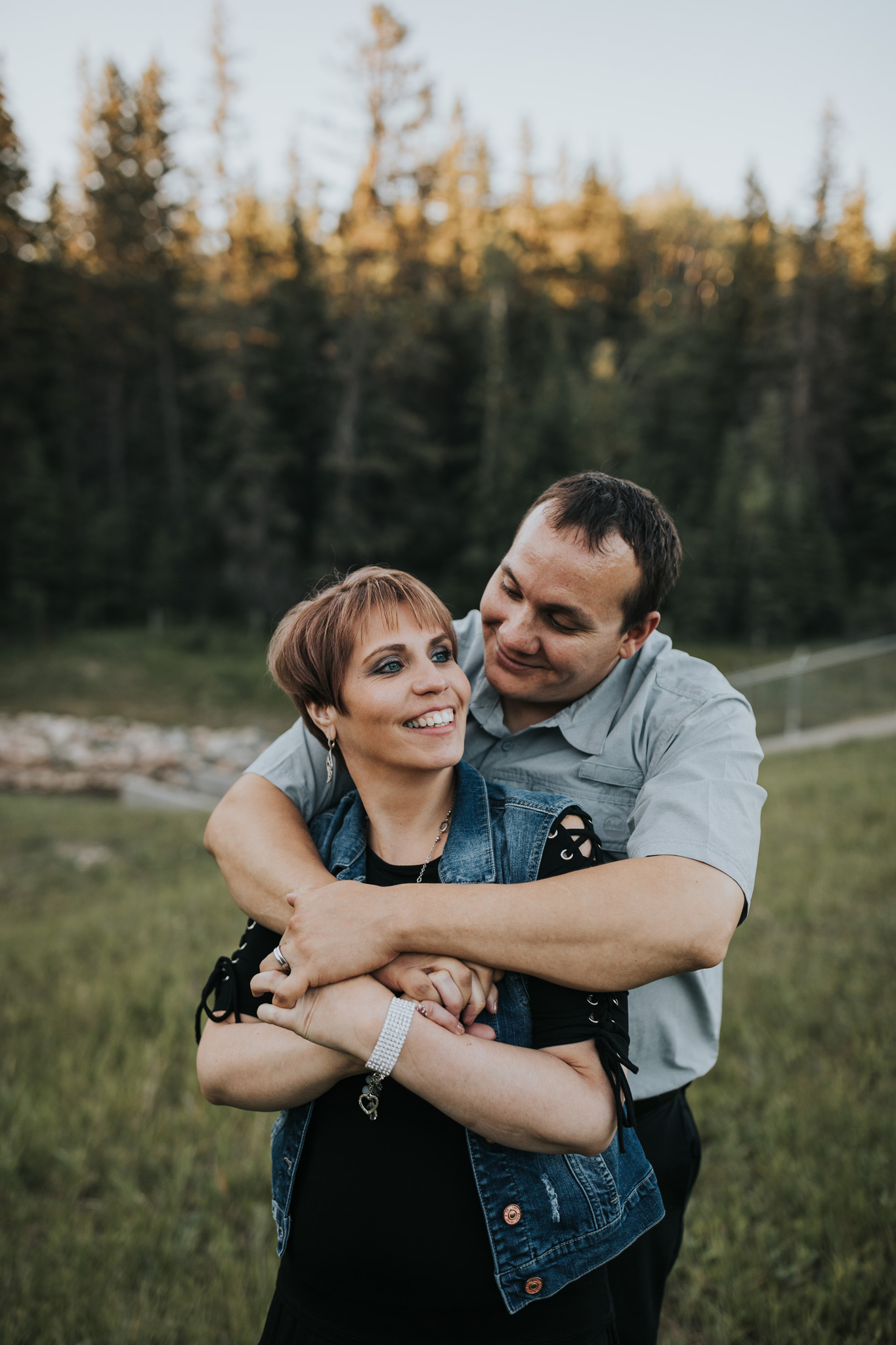 man hugging fiancé from back laughing couple engagement photo