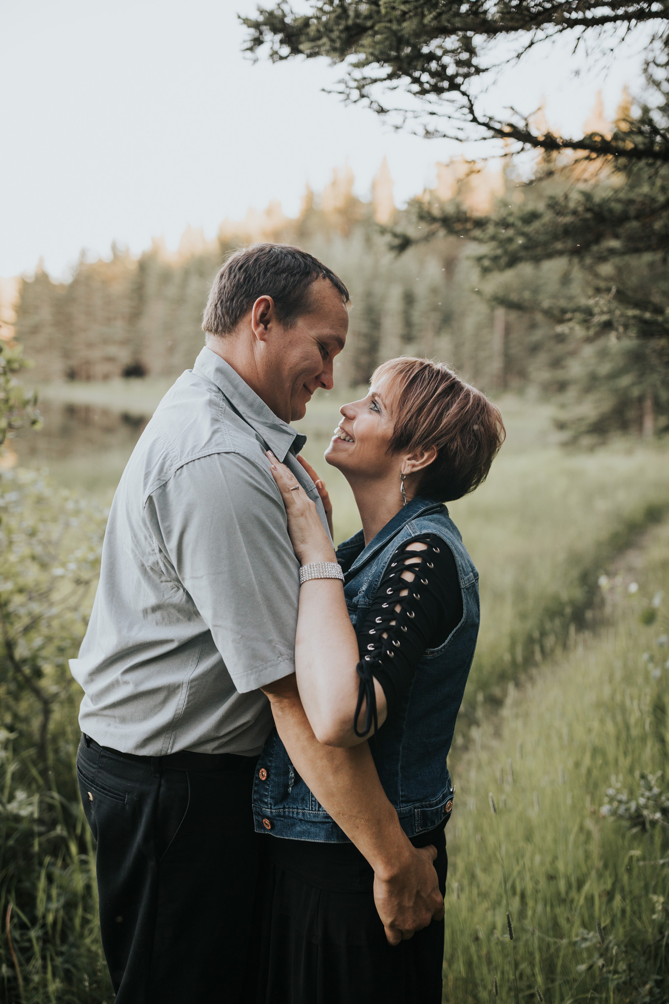 couple standing close together by spruce coulee lake engagement photo