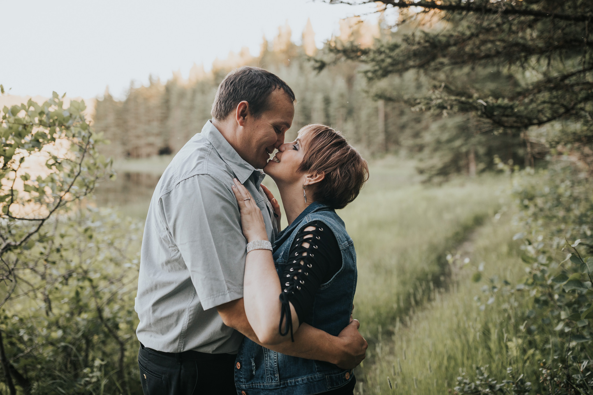 couple standing touching noses spruce coulee lake engagement photo