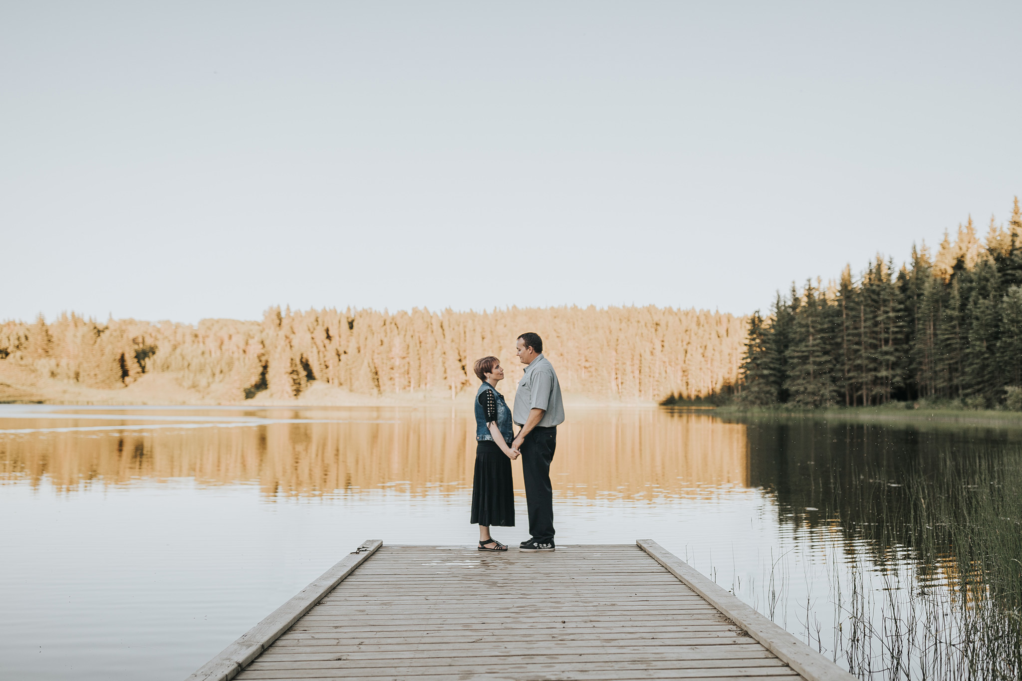 couple holding hands on dock engagement photo