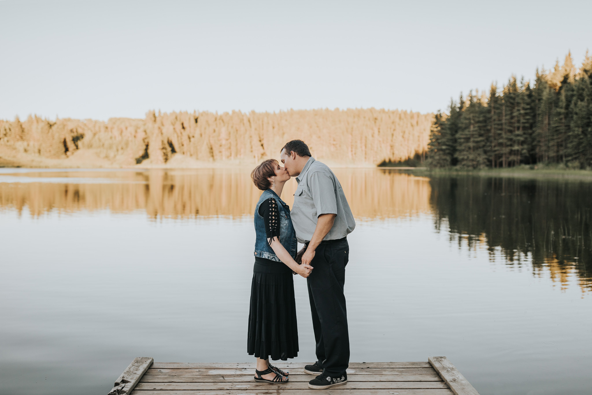 couple kissing on dock in front of lake cypress hills