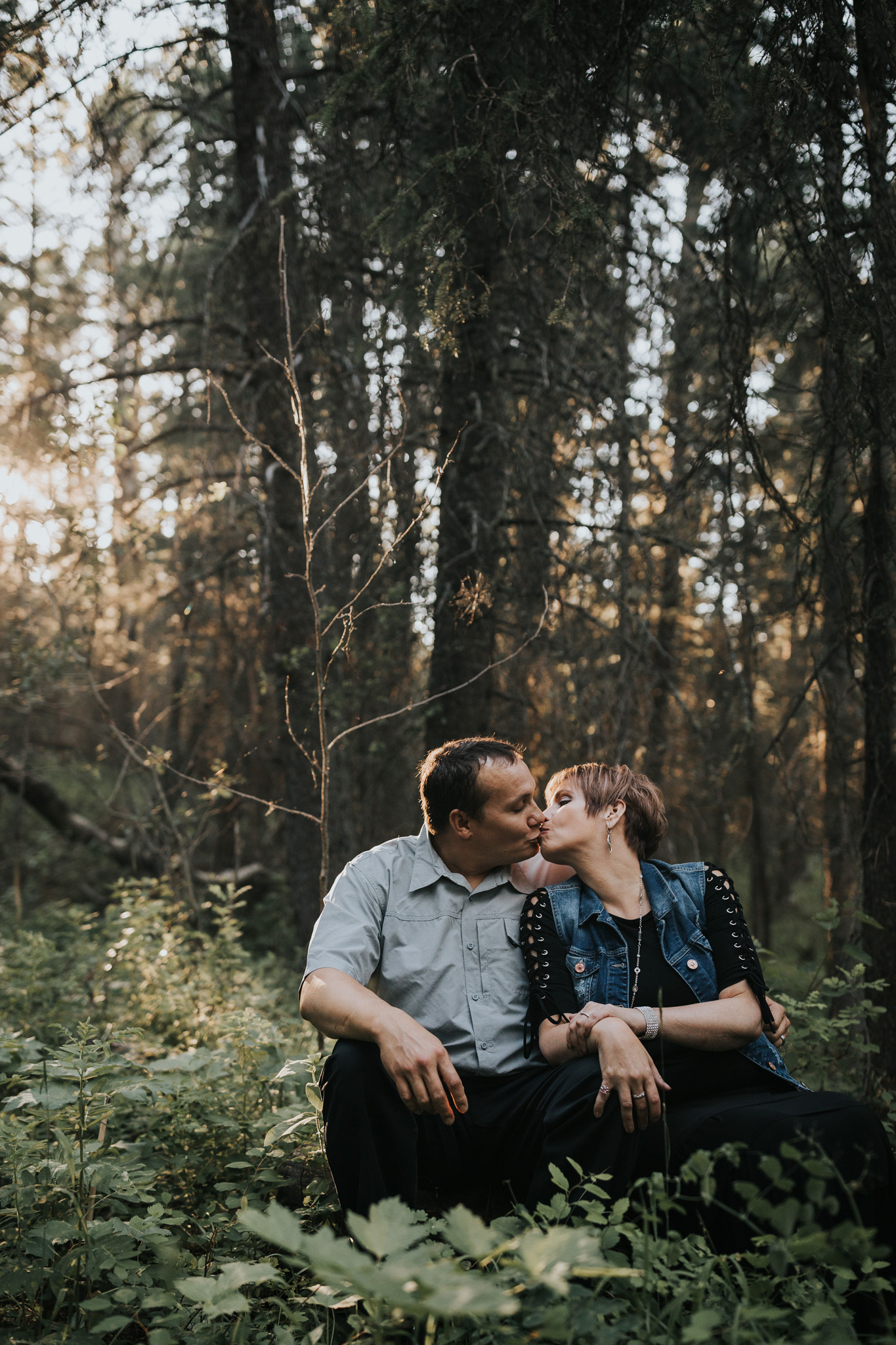 couple sitting on tree log kissing cypress hills engagement