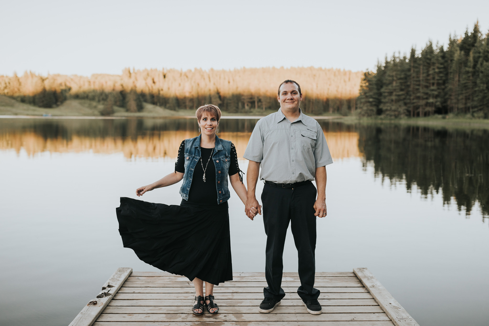 engaged couple standing on dock at spruce coulee lake holding hands as she flips her dress
