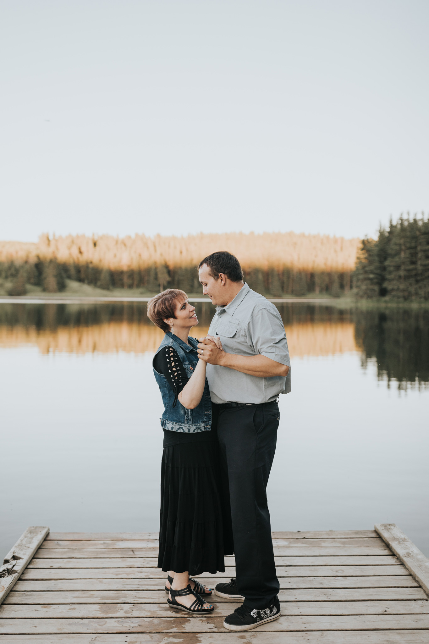 couple dancing on dock spruce coulee lake reflection engagement photo