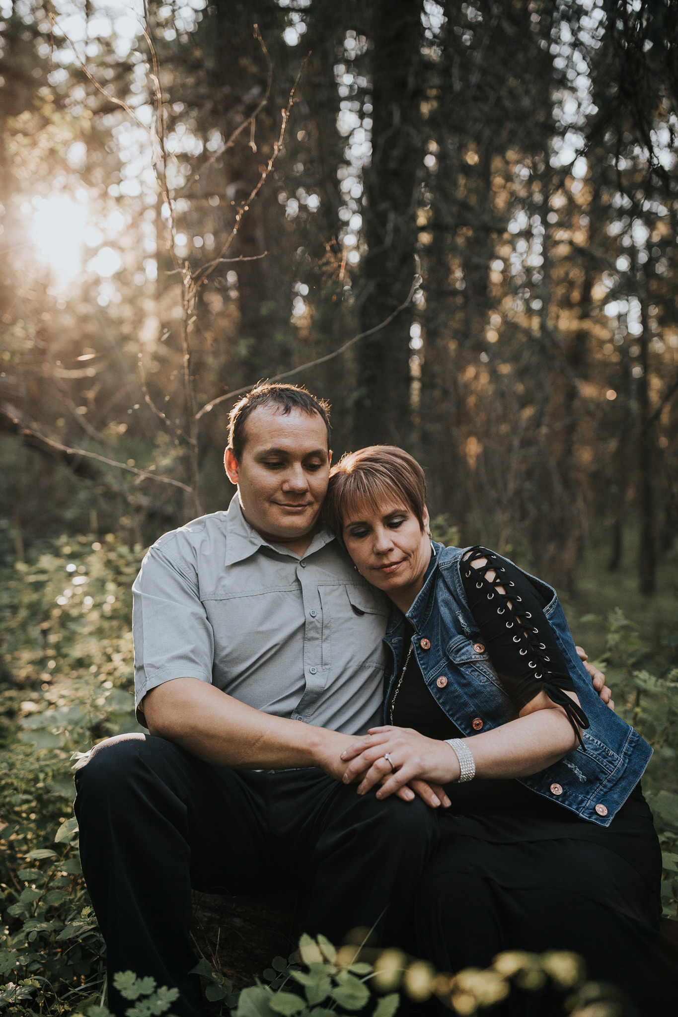 couple sitting on tree log cuddling cypress hills engagement