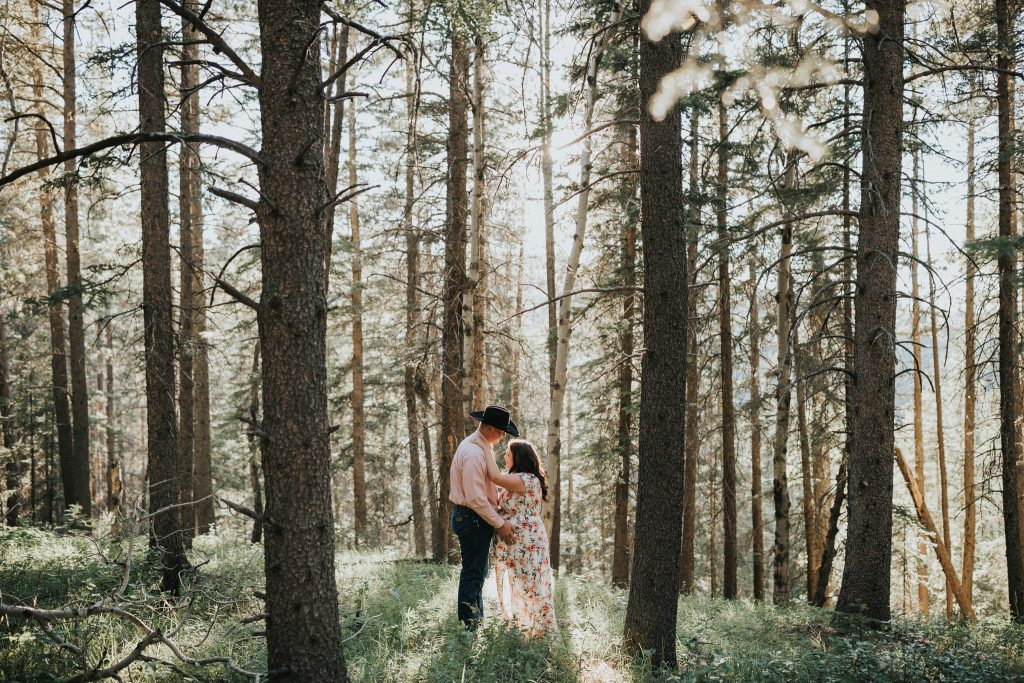 expecting couple embraces in cypress hills forest alberta maternity