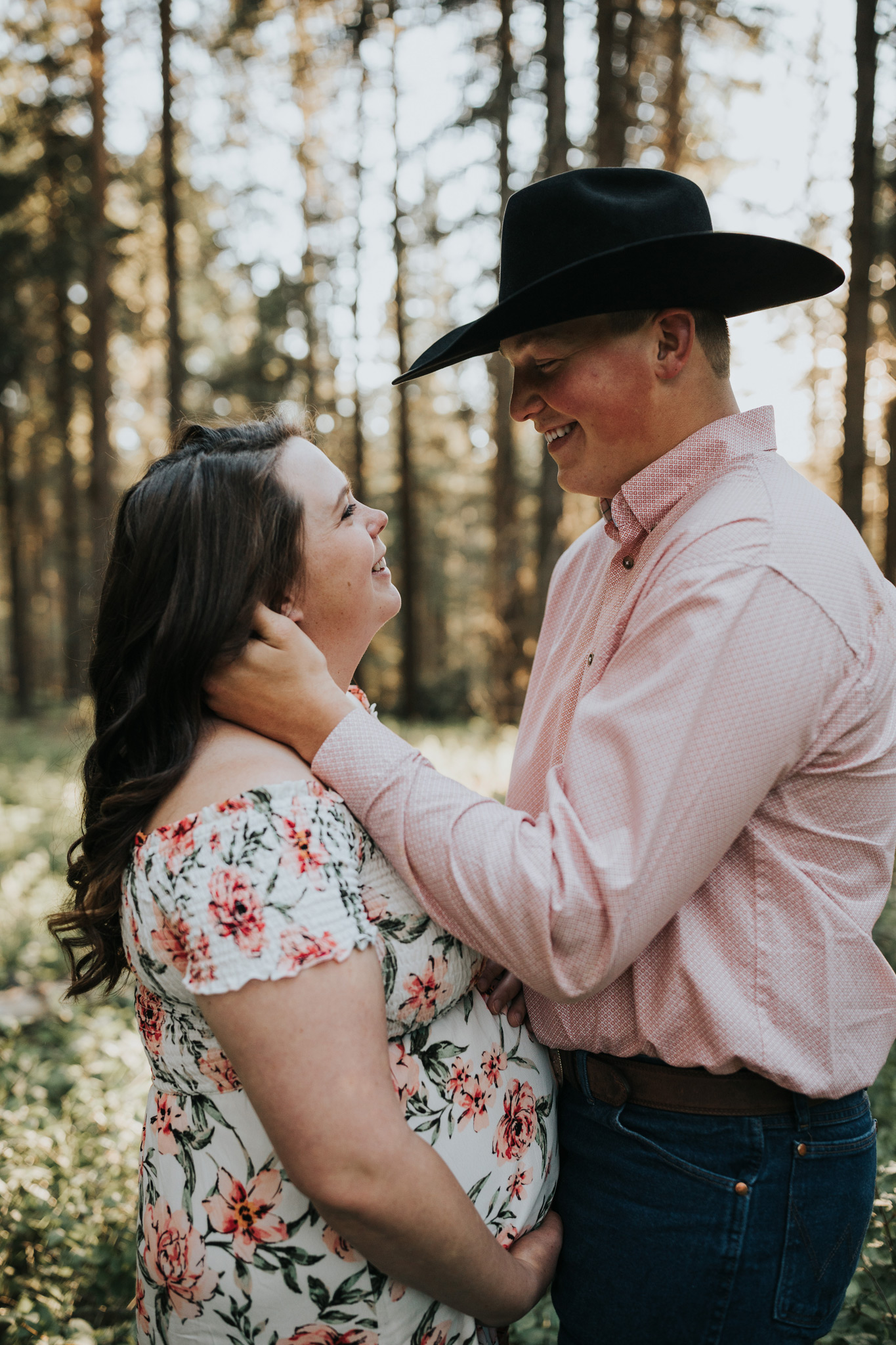 expecting couple facing each other smiling happily elkwater maternity