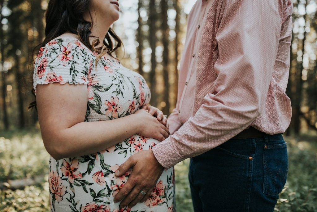 couple facing each other holding expecting wife's belly elkwater alberta maternity