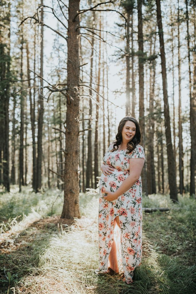 pregnant woman smiling holding belly elkwater maternity