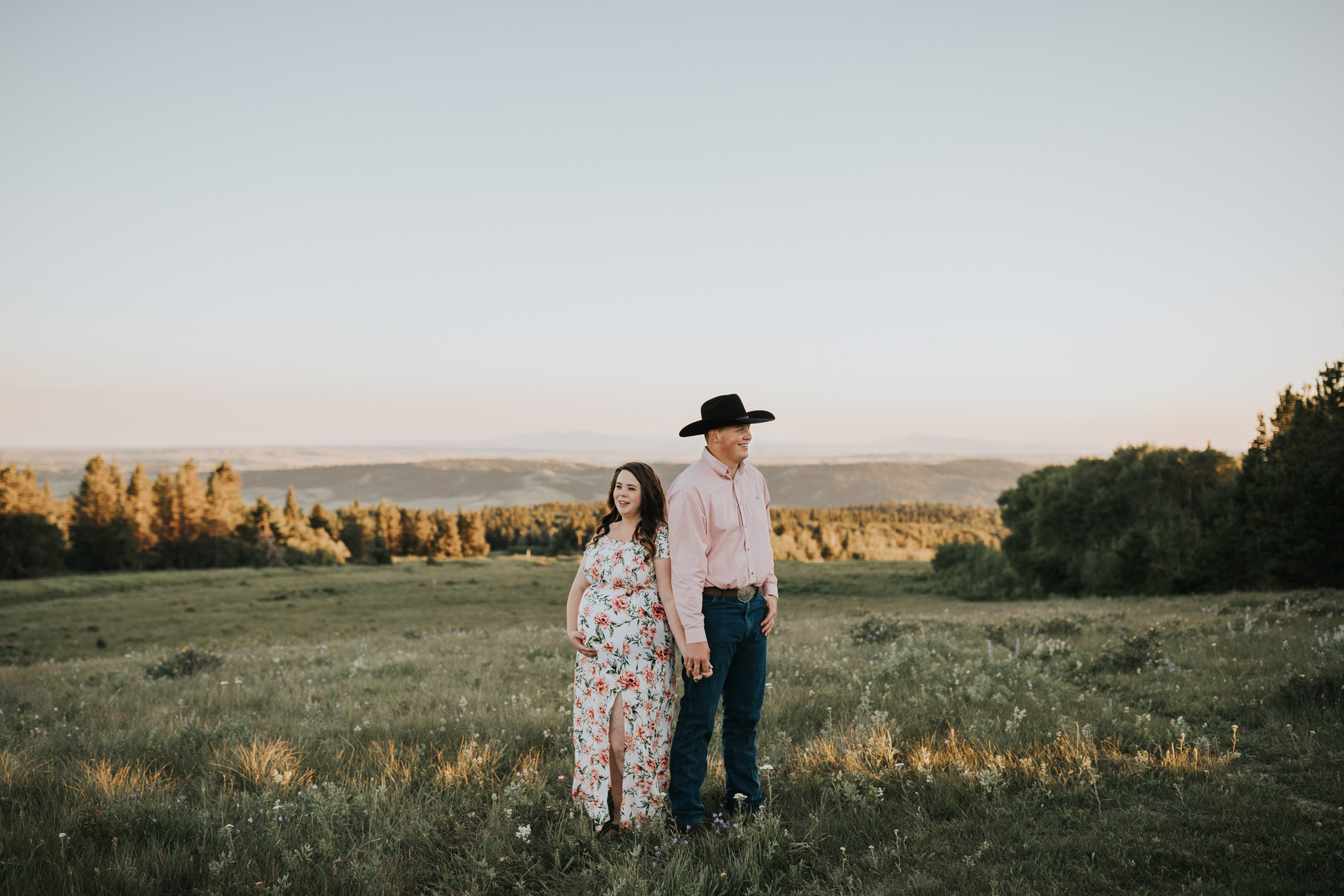 expecting couple holding hands back to back head of the mountain cypress hills alberta maternity