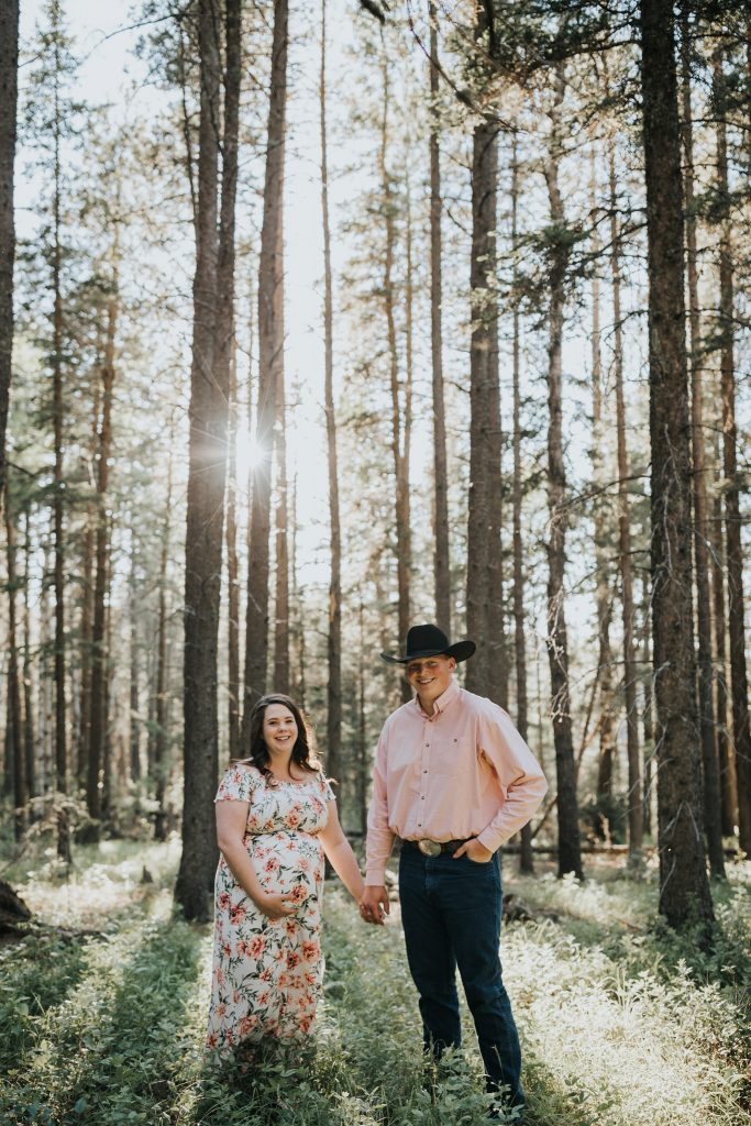expecting couple holding hands smiling in forest elkwater maternity