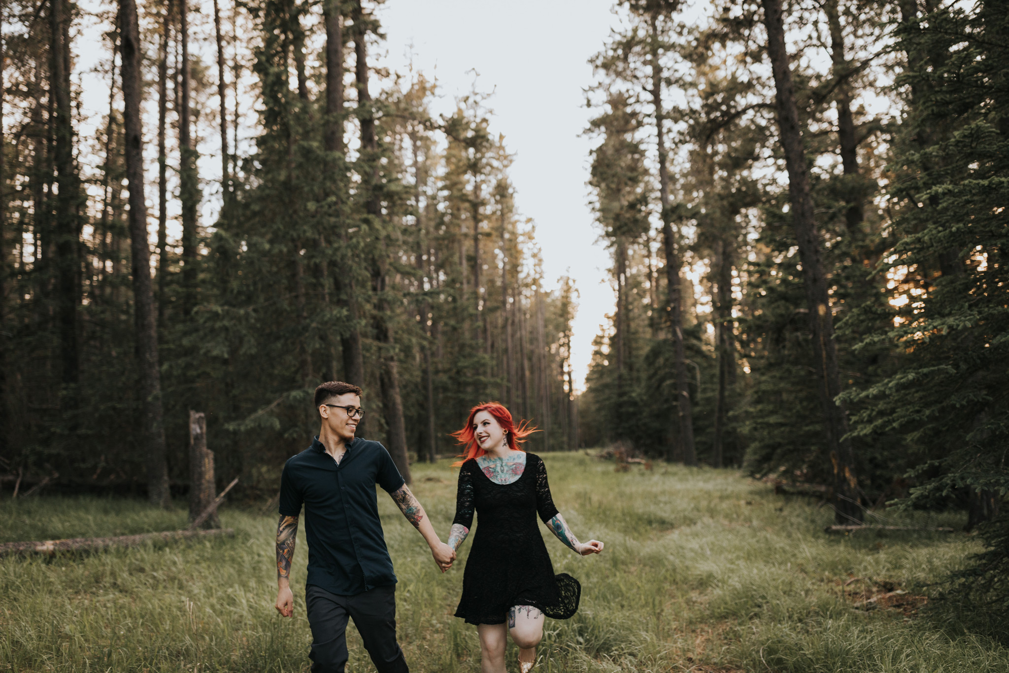 couple holding hands running laughing elkwater engagement photo