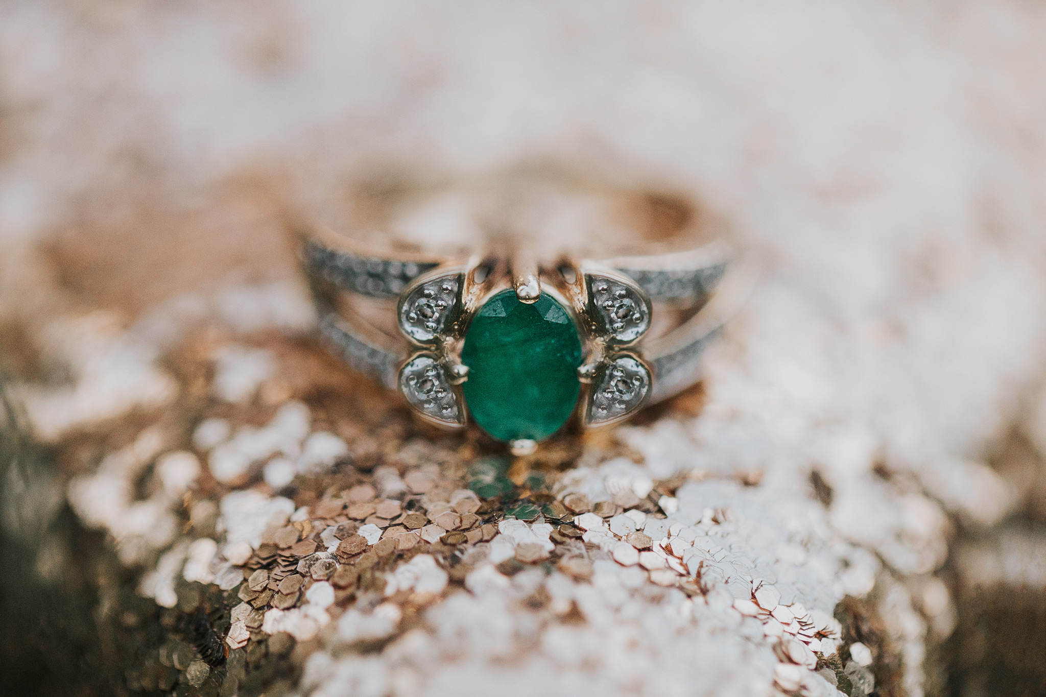 emerald engagement ring closeup gold glitter photo