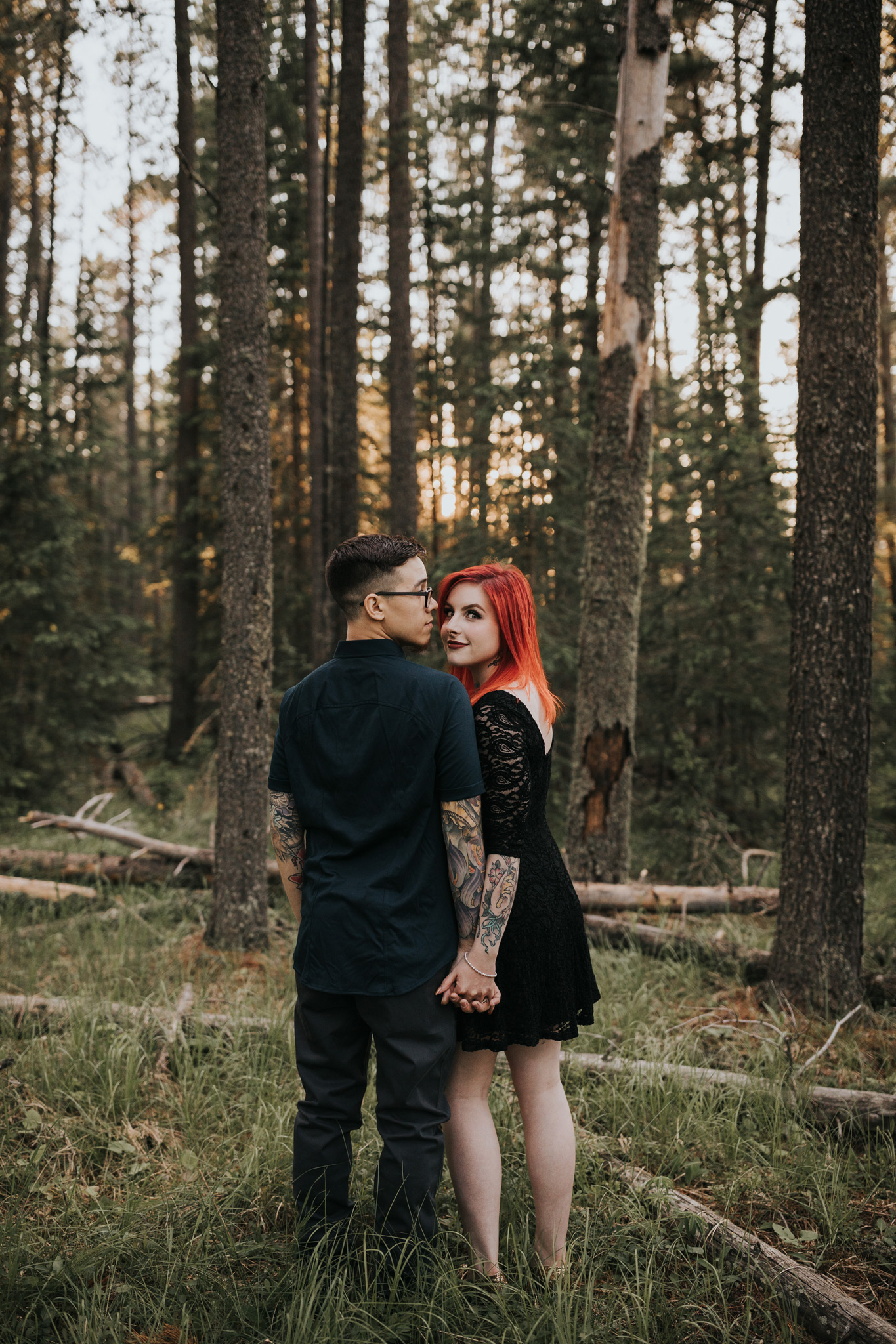 couple holds hands looking over shoulder alberta forest engagement