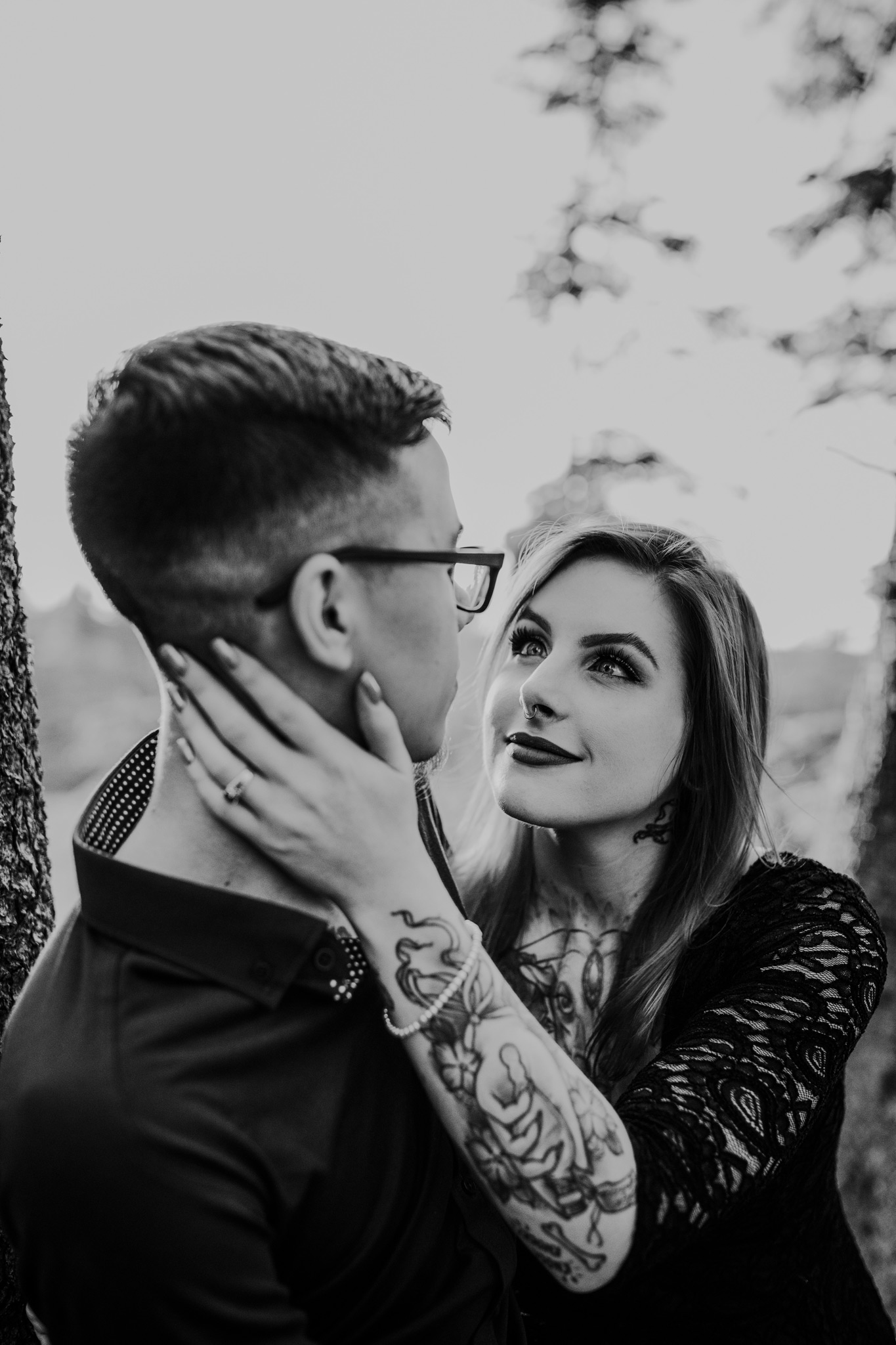 woman pulls fiancé's face to ears engagement ring photo