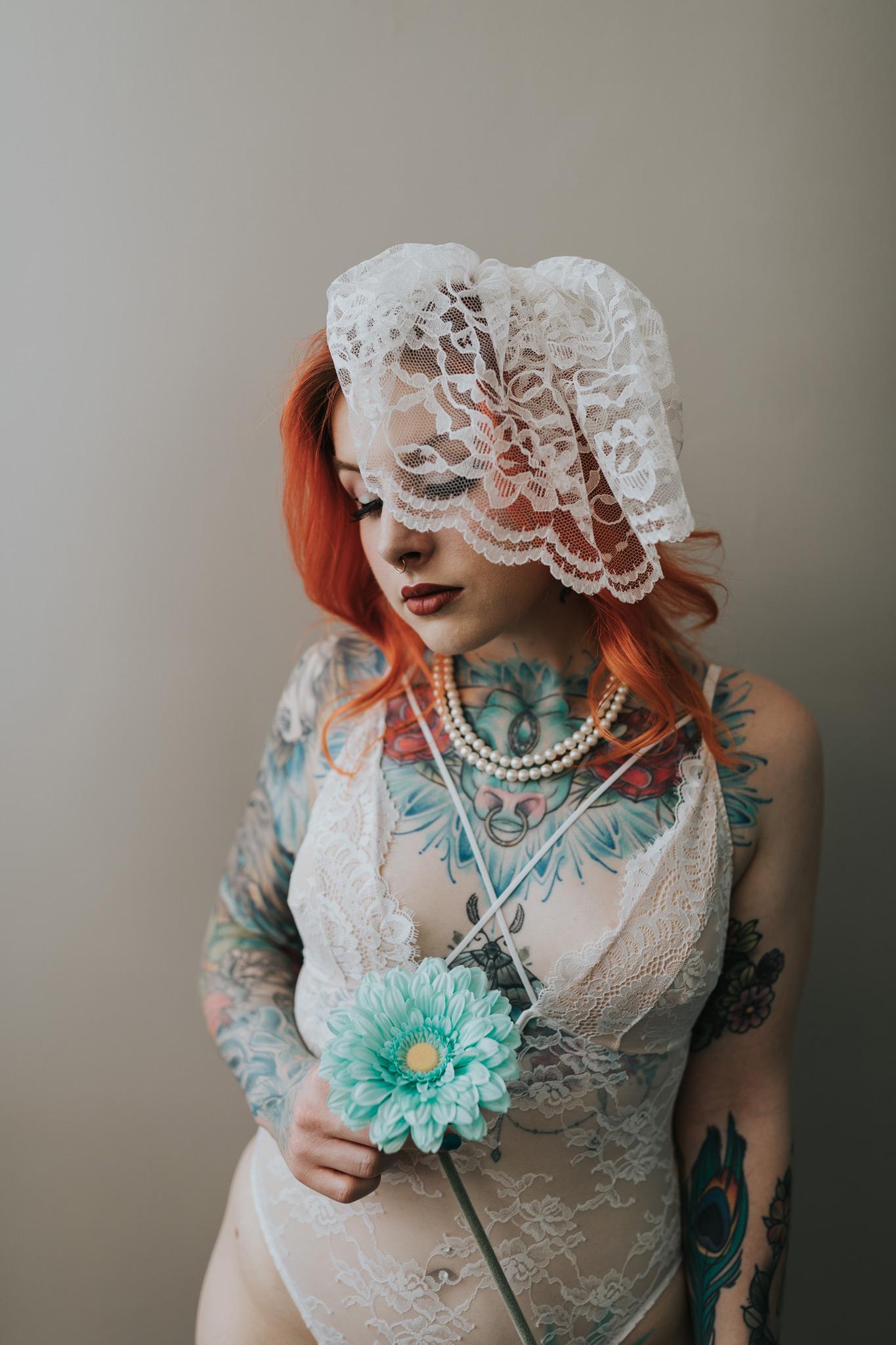 woman holding flower birdcage veil bridal boudoir photo