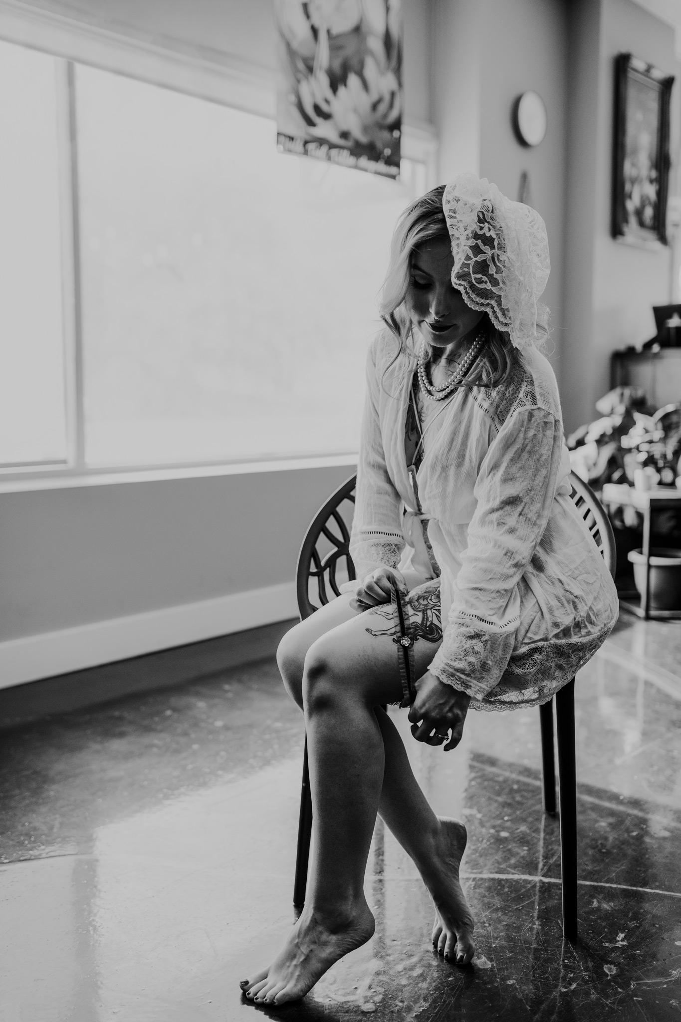 woman putting garter on leg bridal boudoir photo