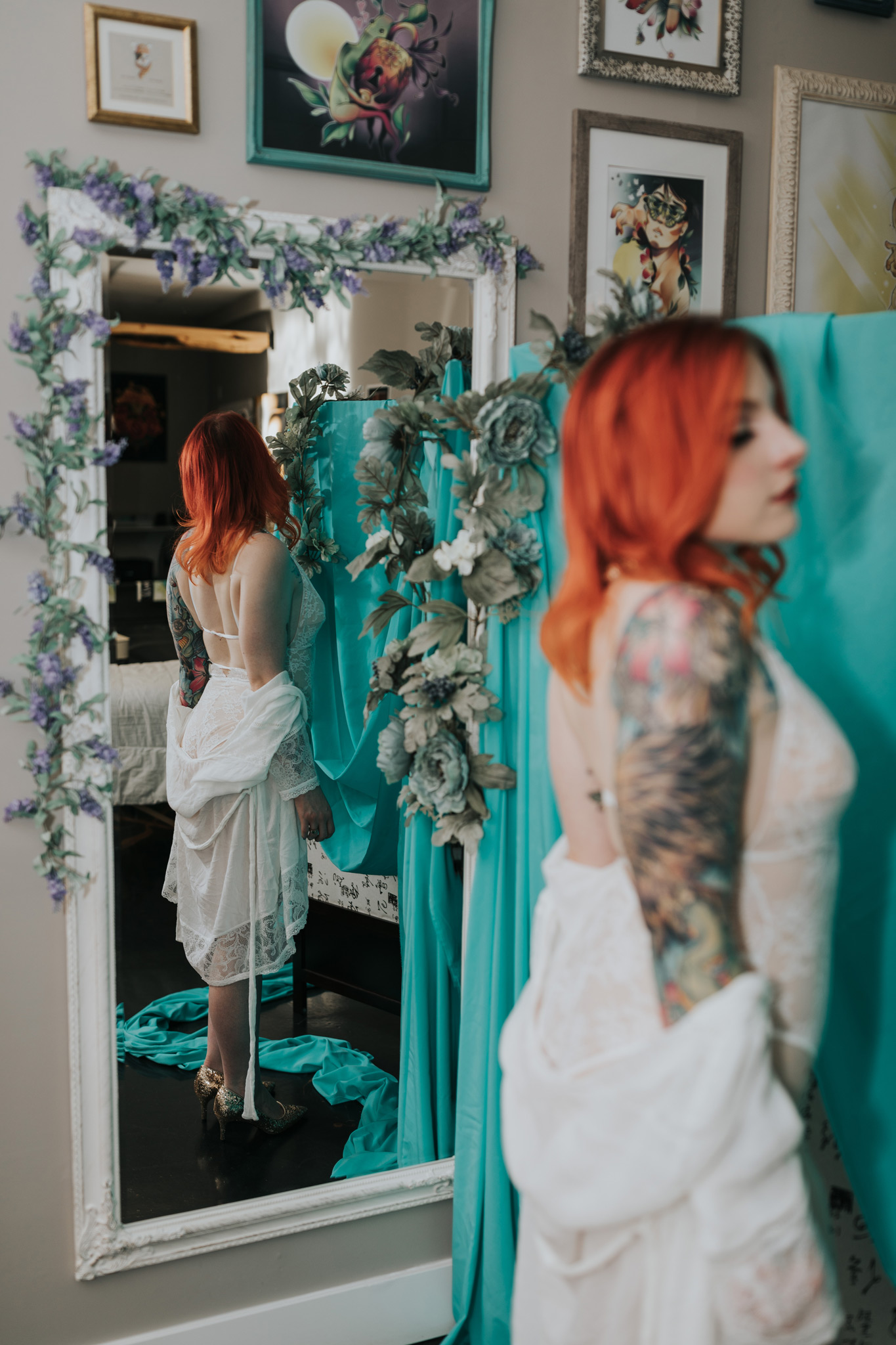 tattooed woman standing by mirror reflection bridal boudoir photo