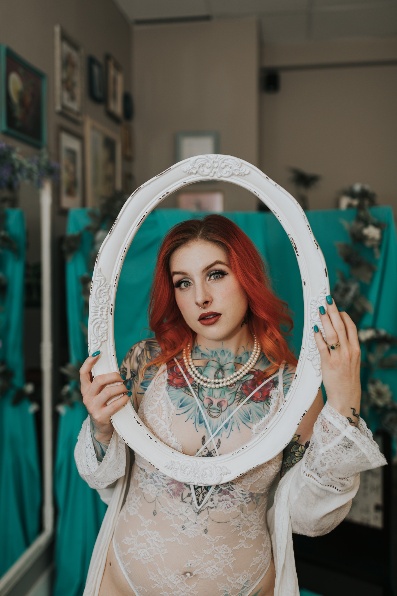 tattooed woman holding frame around face bridal boudoir