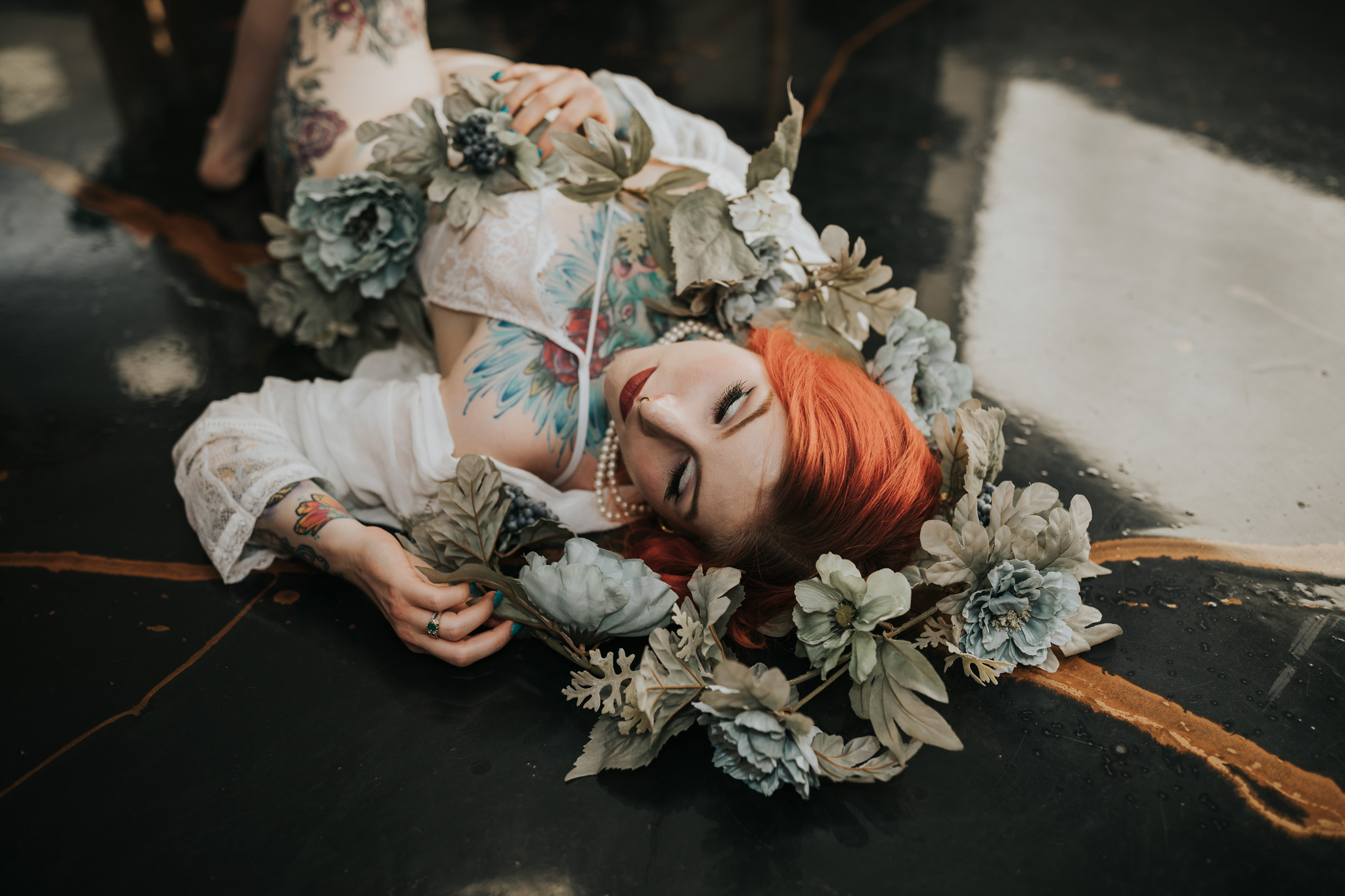 woman laying on ground with garland wrapped bridal boudoir