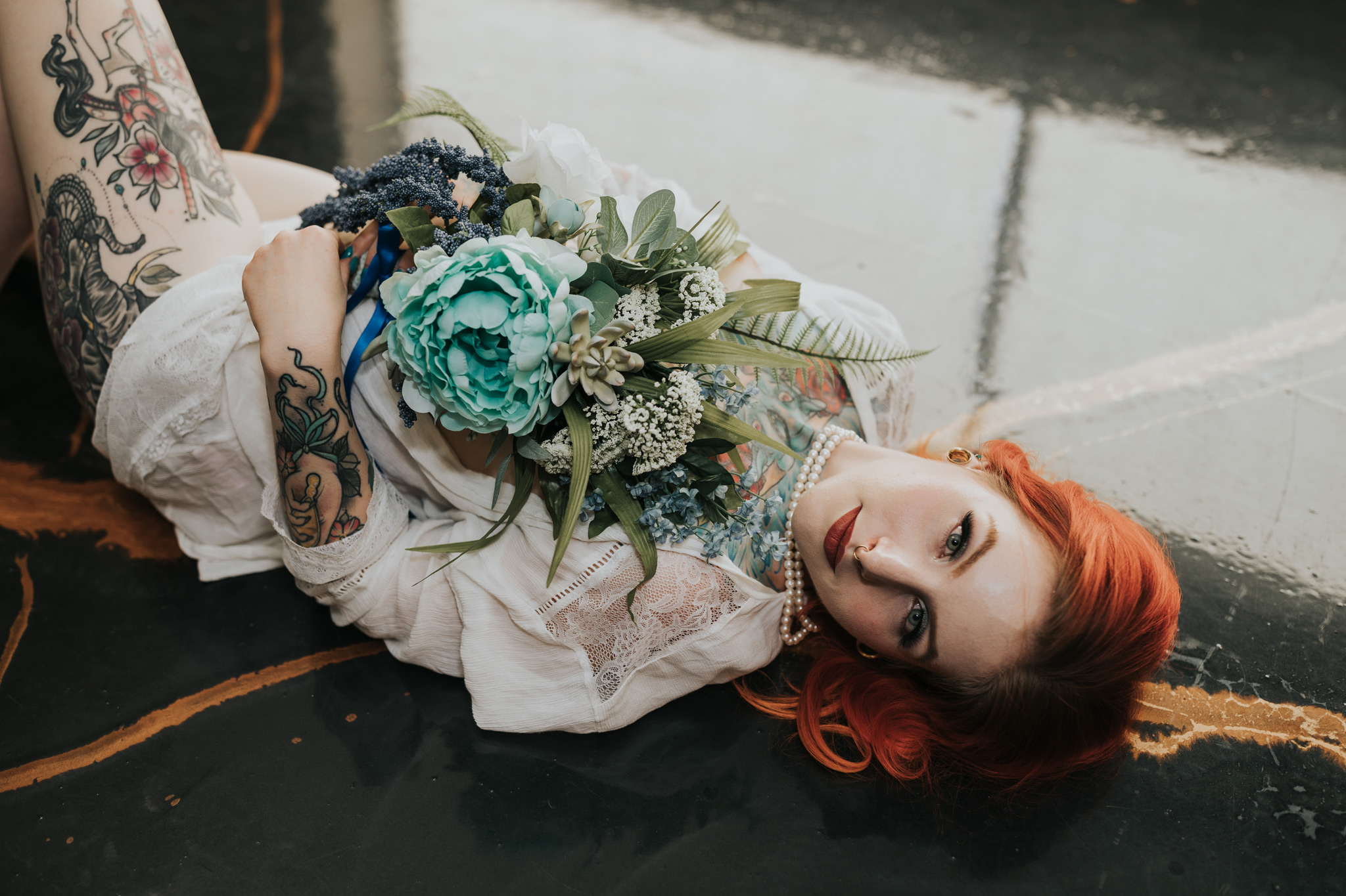 woman laying on floor holding bridal bouquet medicine hat boudoir