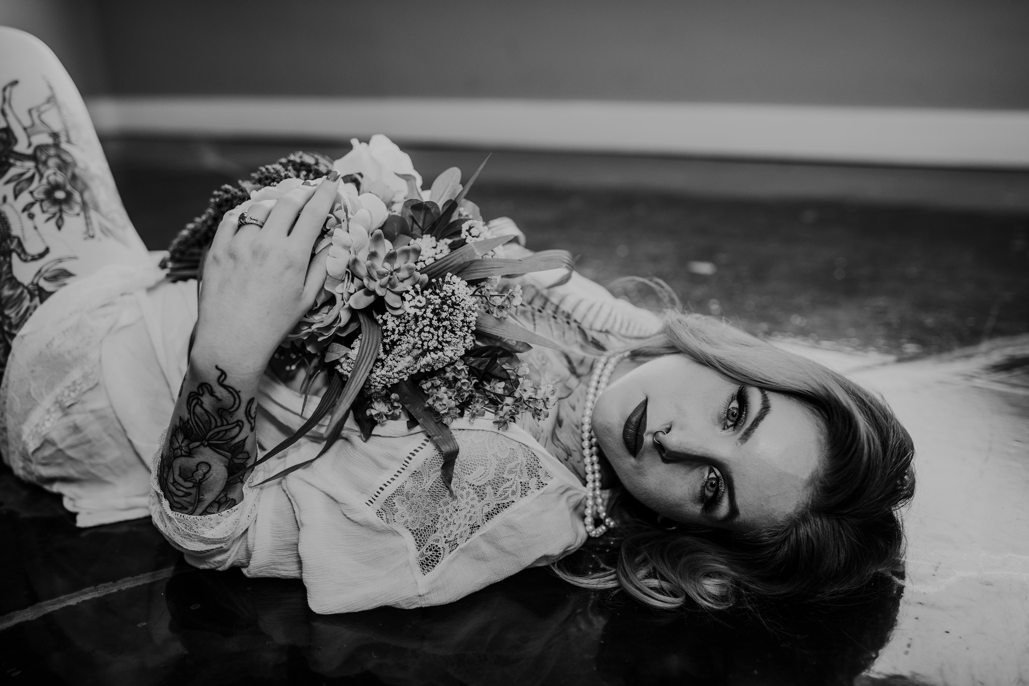 woman laying on floor holding bridal bouquet alberta boudoir