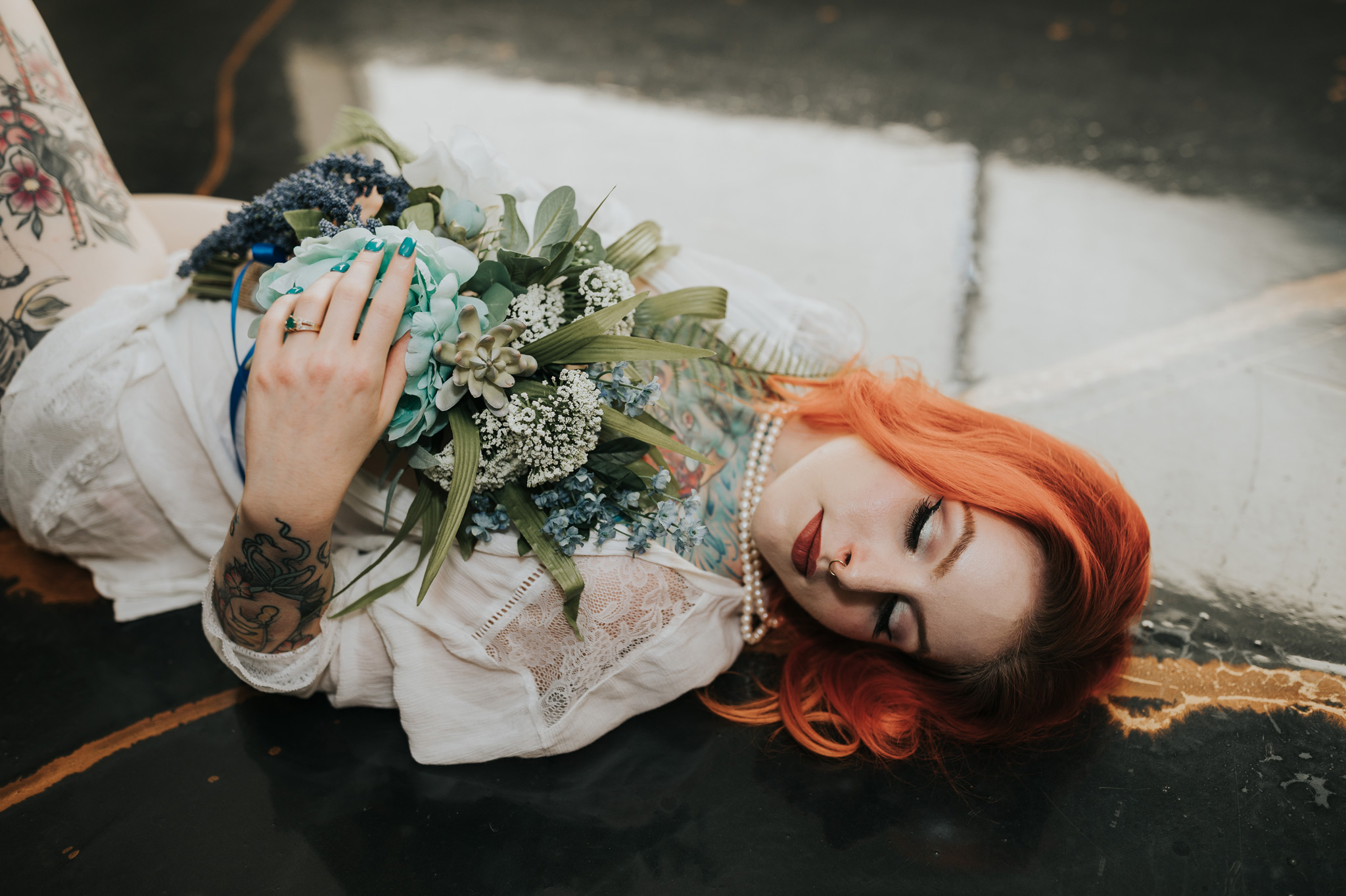 woman laying on floor holding bouquet bridal boudoir