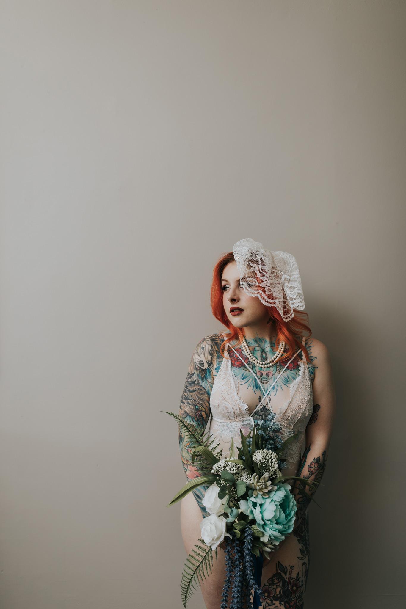 woman holding wedding bouquet birdcage veil bridal boudoir