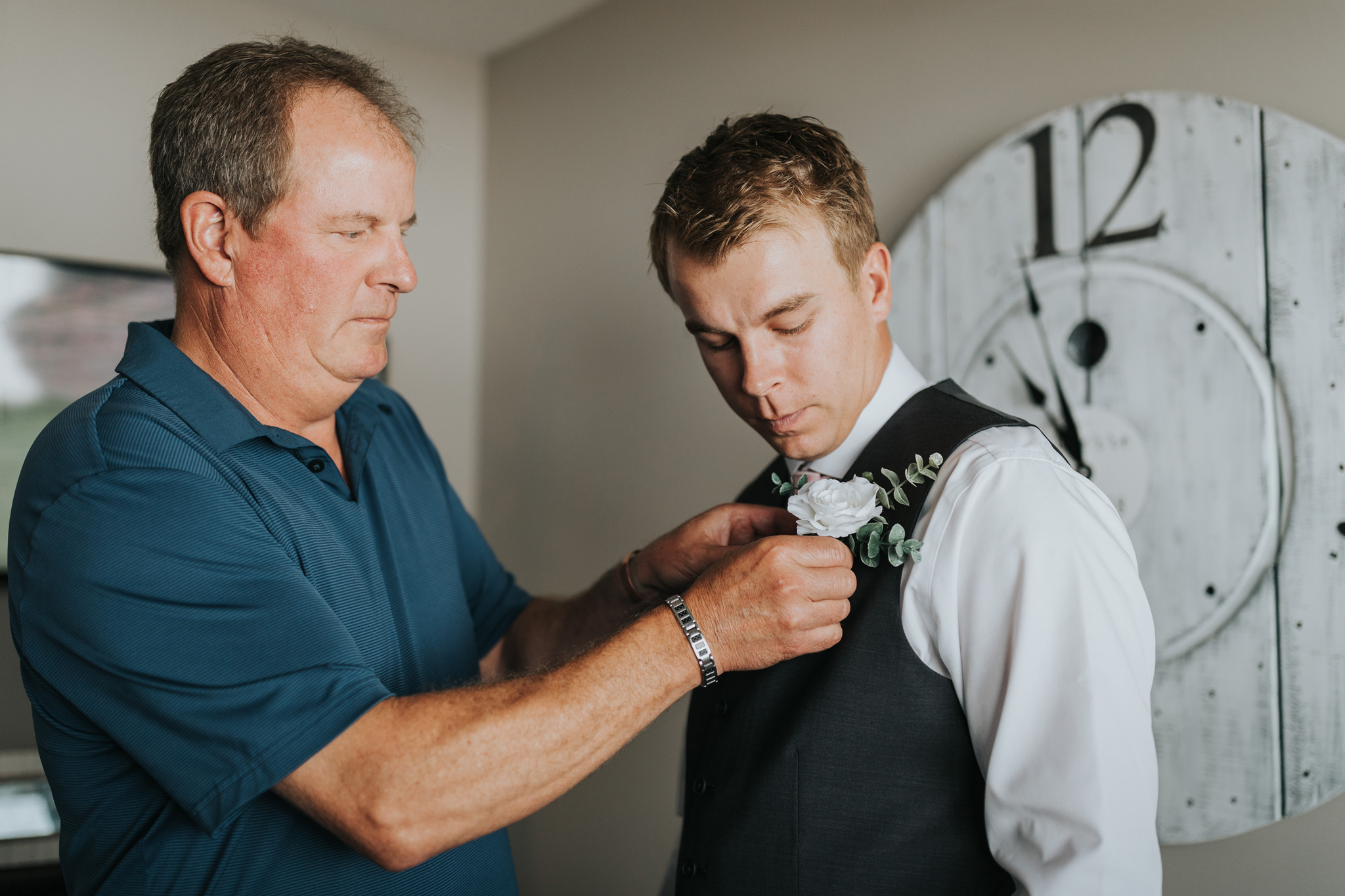 grooms dad pinning boutonniere on groom