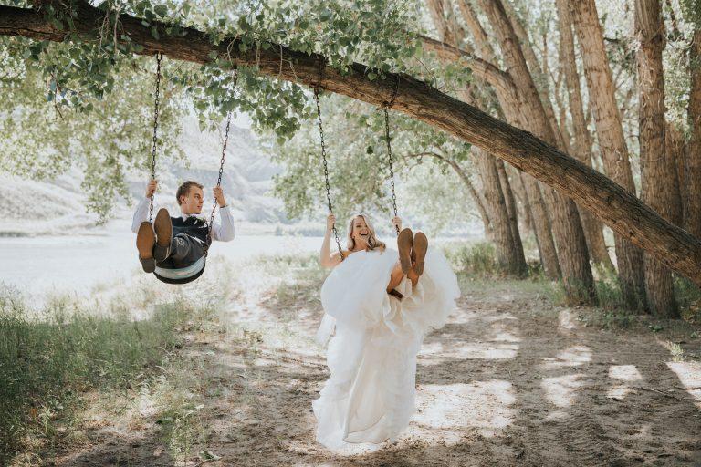 bride and groom swinging in their backyard tree swing medicine hat alberta wedding photo