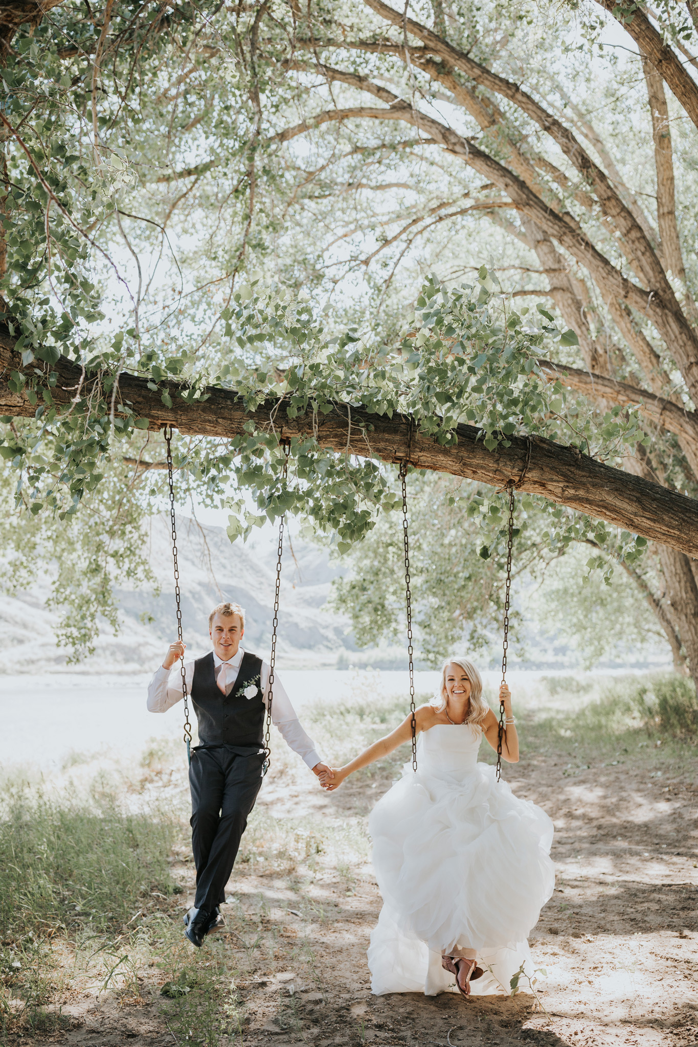 bride and groom swinging in their backyard tree swing medicine hat alberta wedding photo
