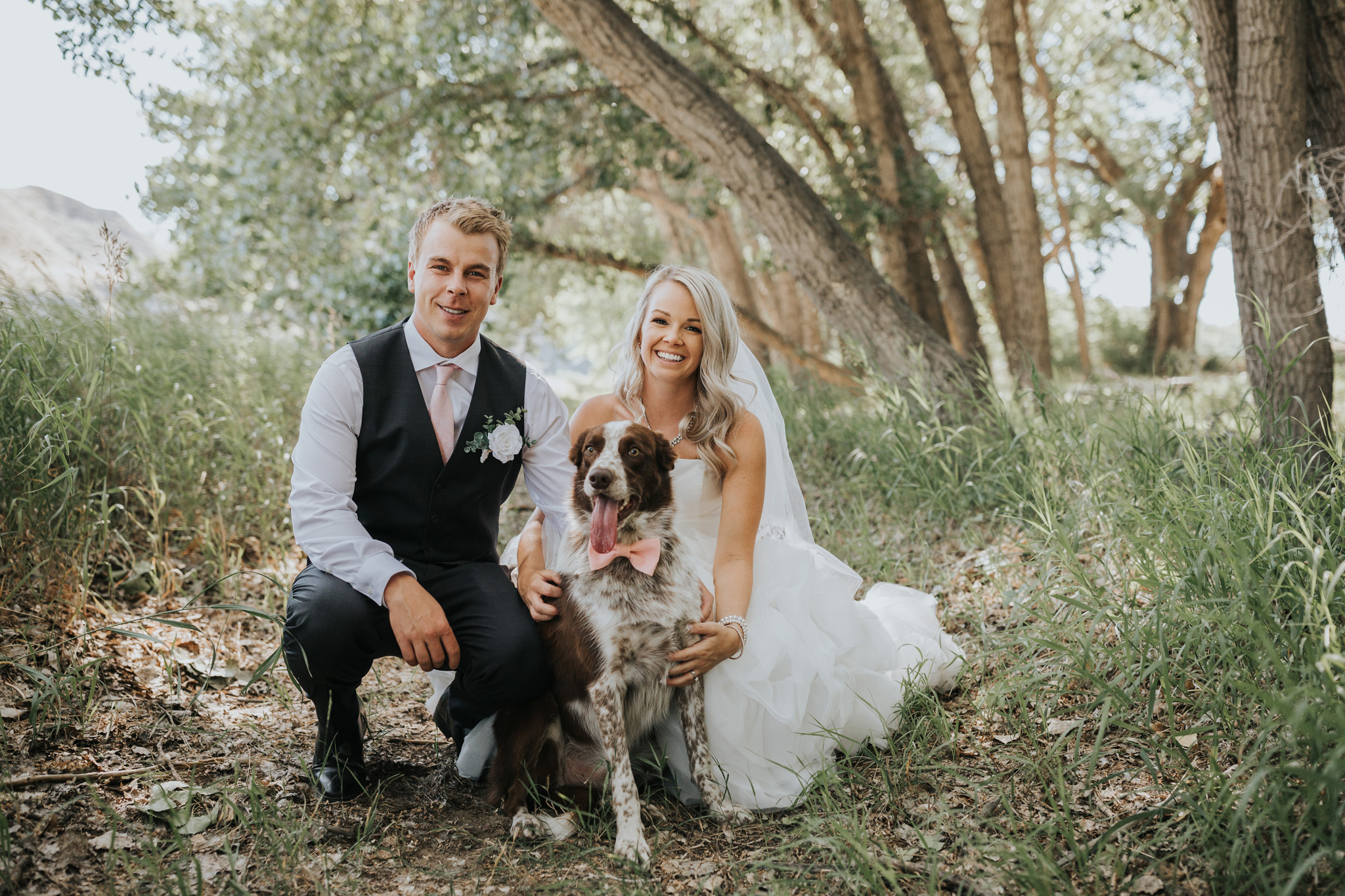 bride and groom pose with their dog wearing a bowtie