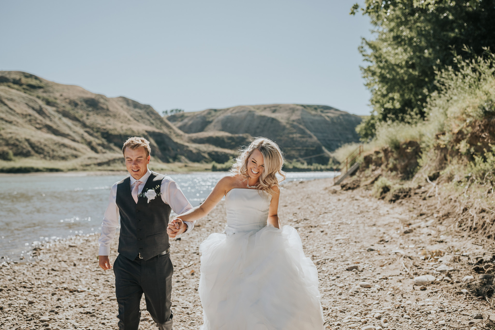 bride and groom holding hands running laughing by the river