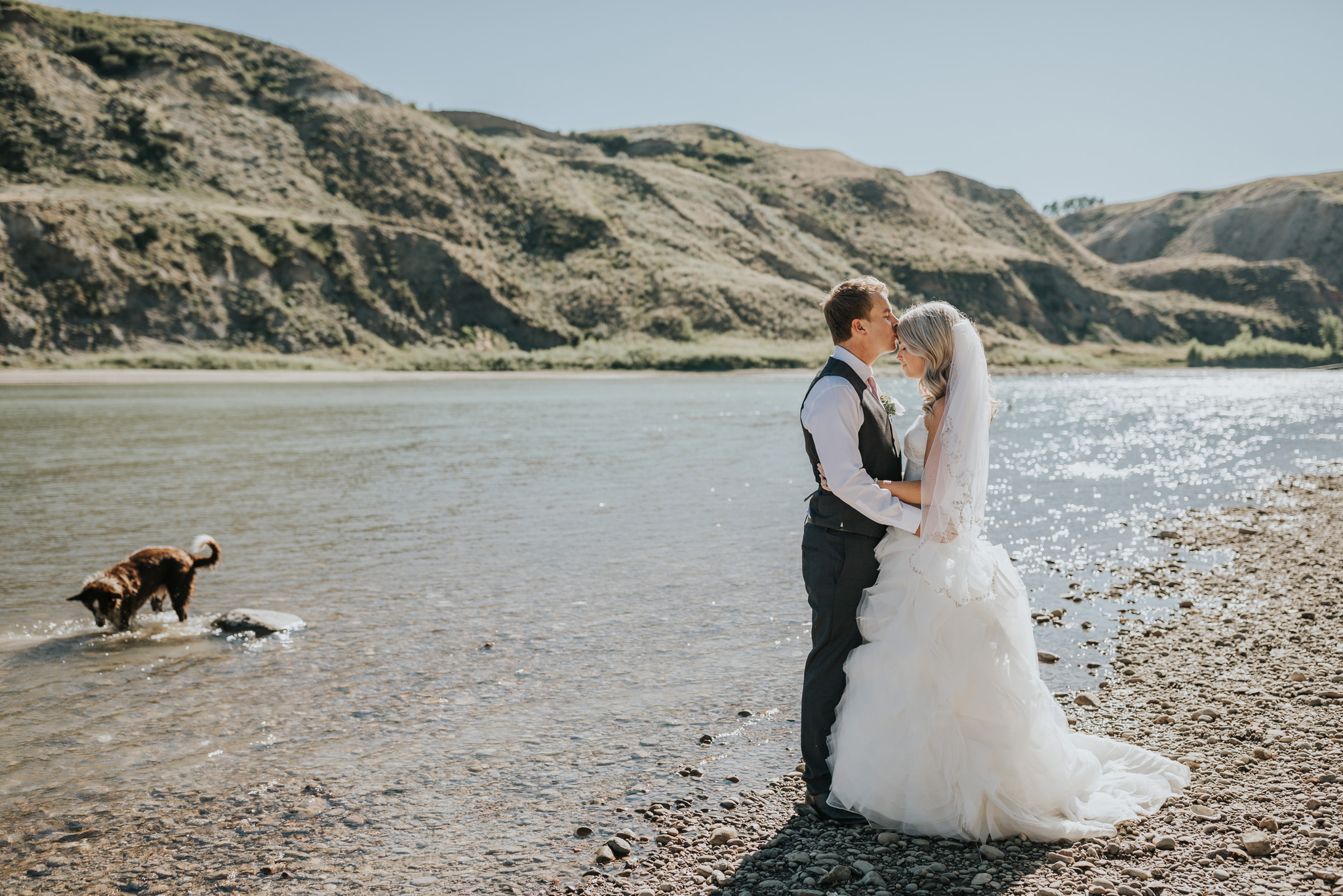 bride and groom holding each other by the south saskatchewan river and coulees