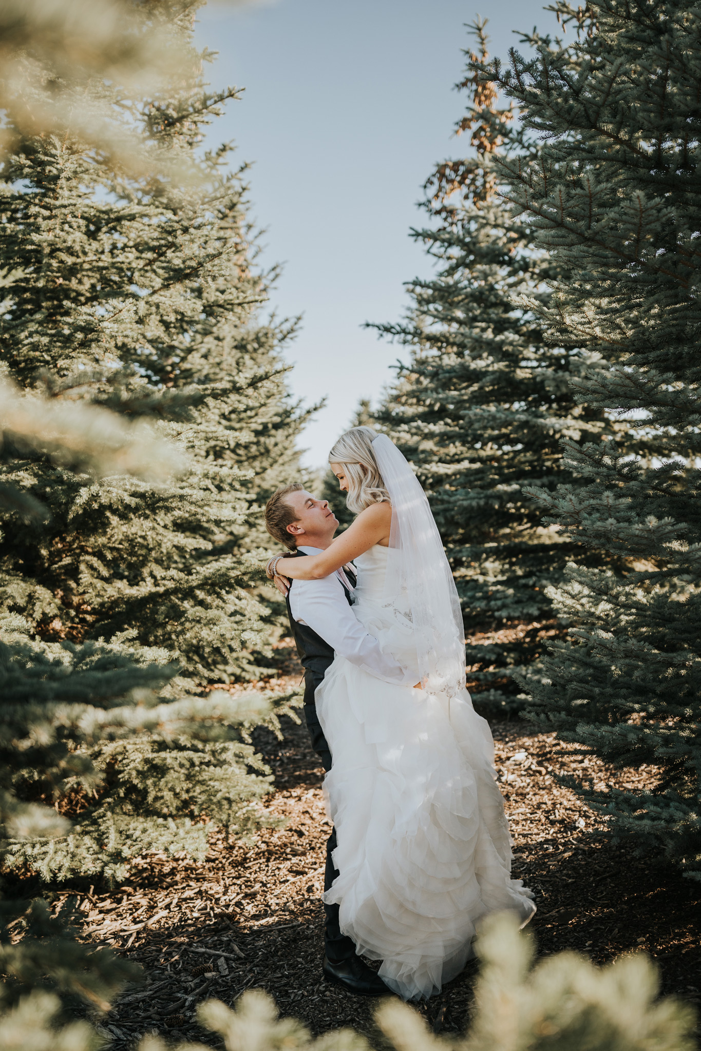 groom lifts bride among the trees medicine hat wedding photographer