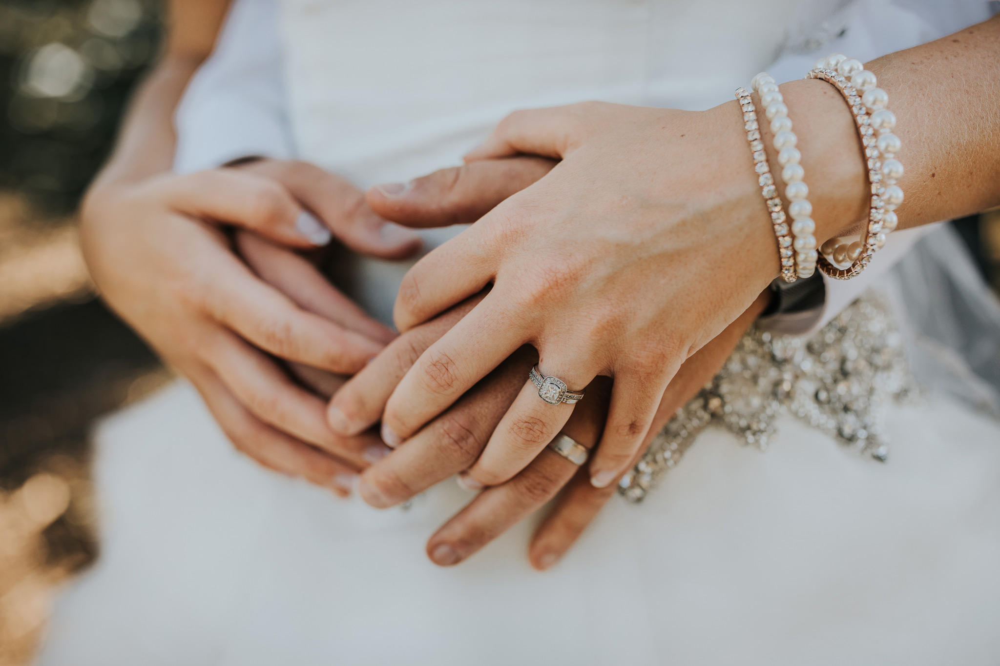 closeup of bride and grooms hands with wedding rings