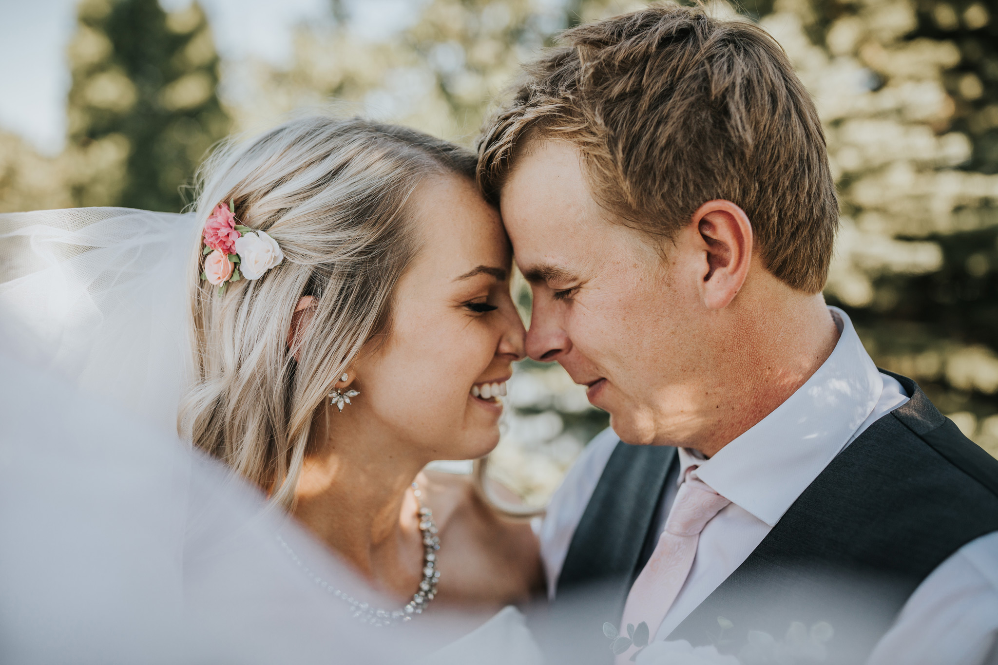 bride and groom standing foreheads together smiling