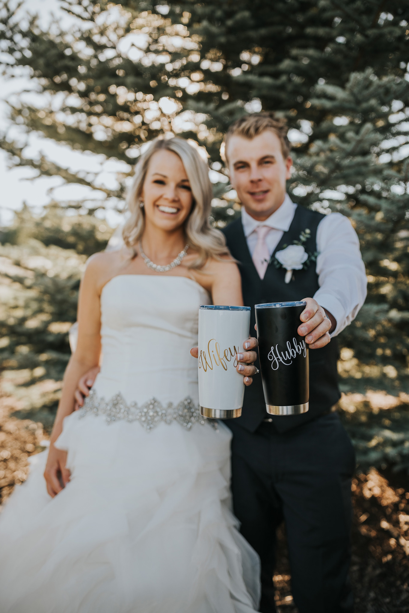 bride and groom holding out matching wifey and hubby travel mugs